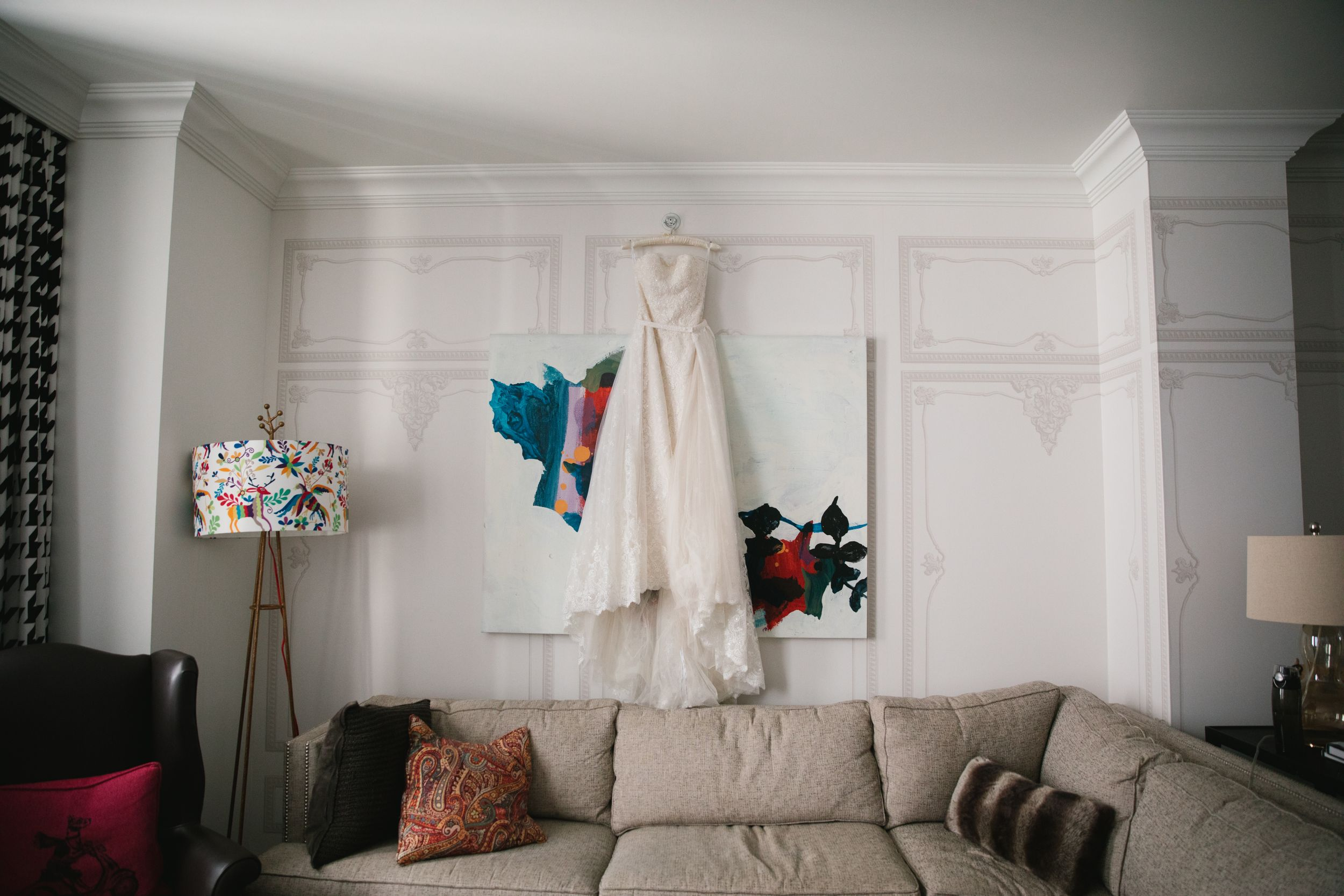 white wedding dress hanging in hotel room above sofa monaco pittsburgh