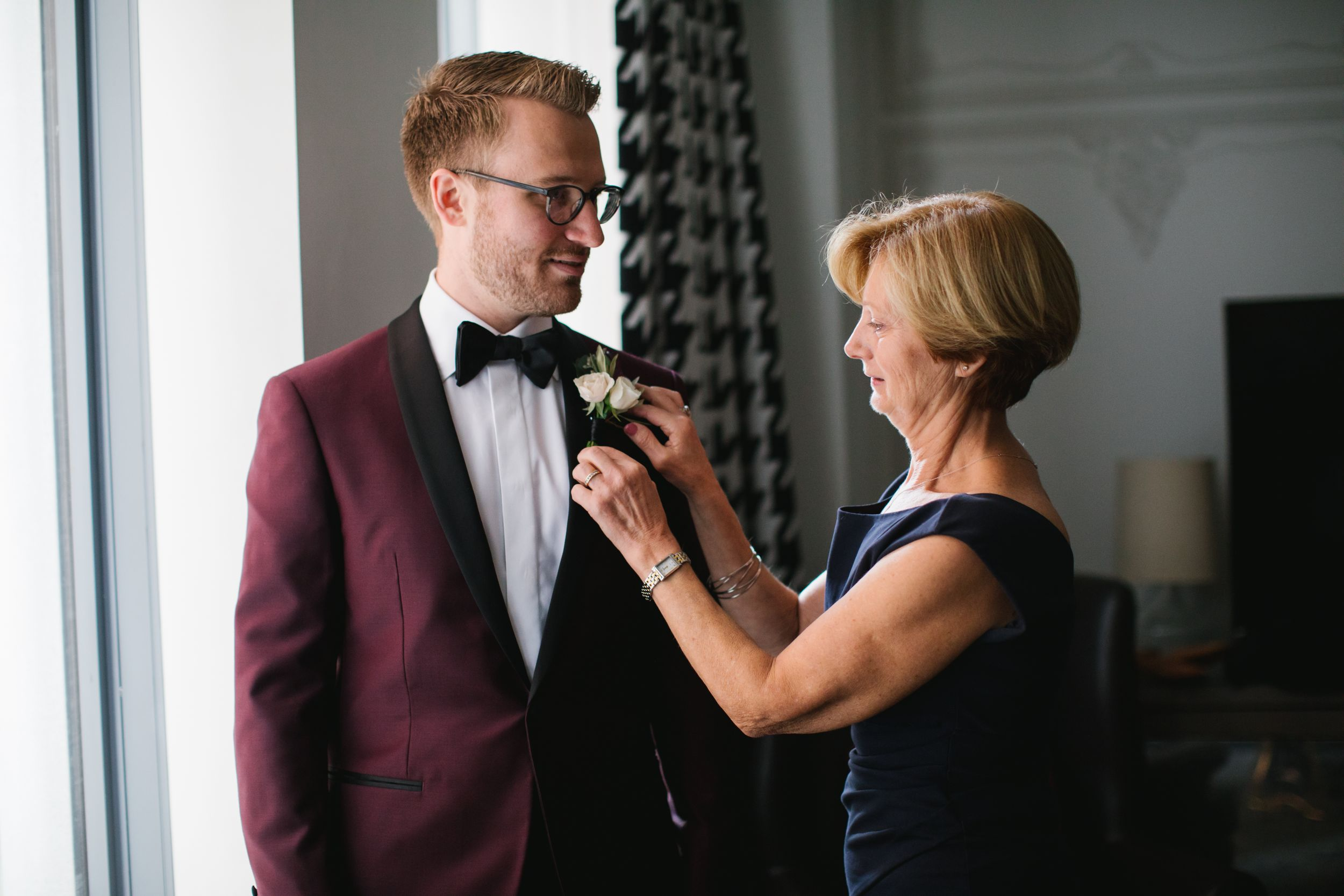 mother of groom helping him put on his boutonniere by window in hotel room