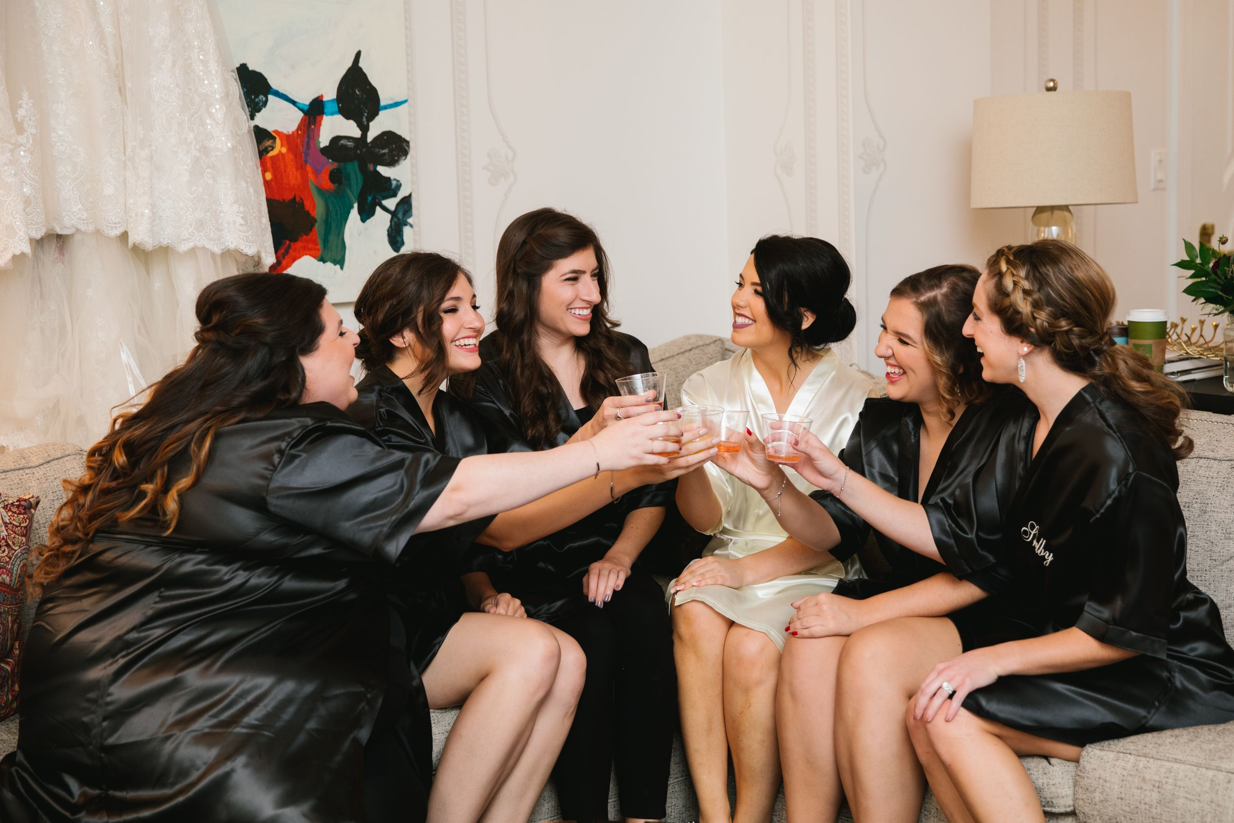 bride with bridesmaids in robes sitting on sofa and cheersing with champagne