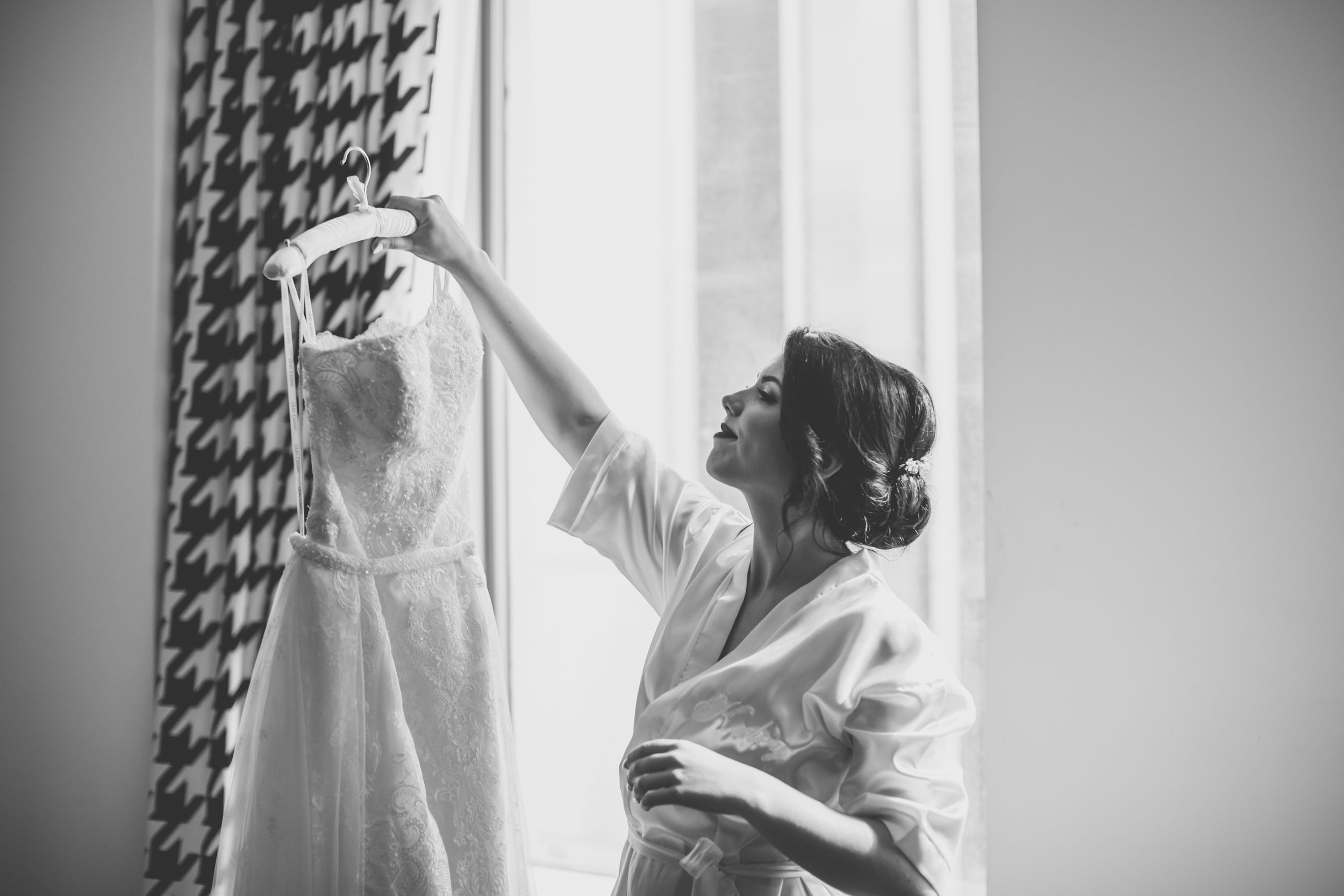 bride holding up wedding dress in front of window black and white
