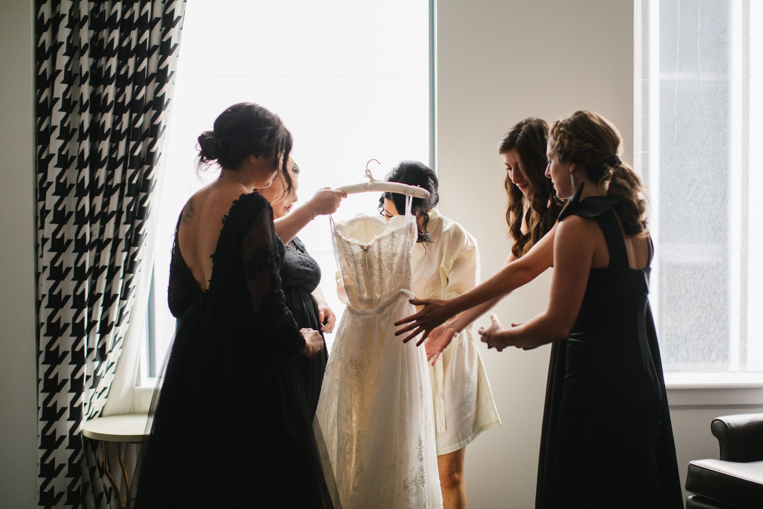 bride with bridesmaids putting on wedding dress in front of window
