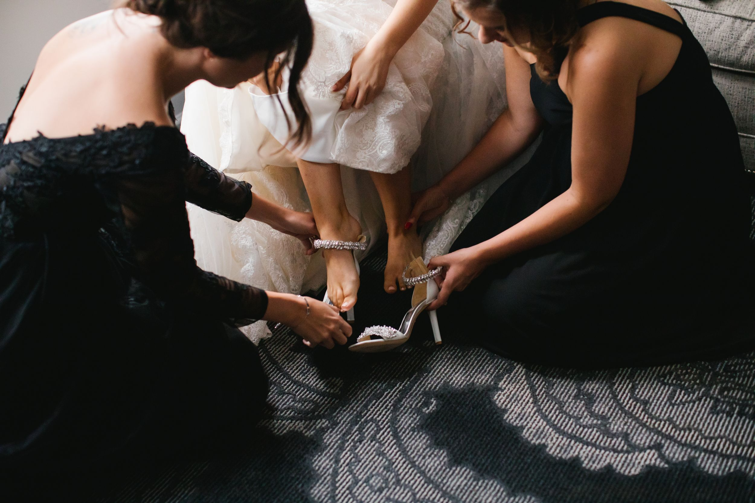bridesmaids helping bride put on her shoes