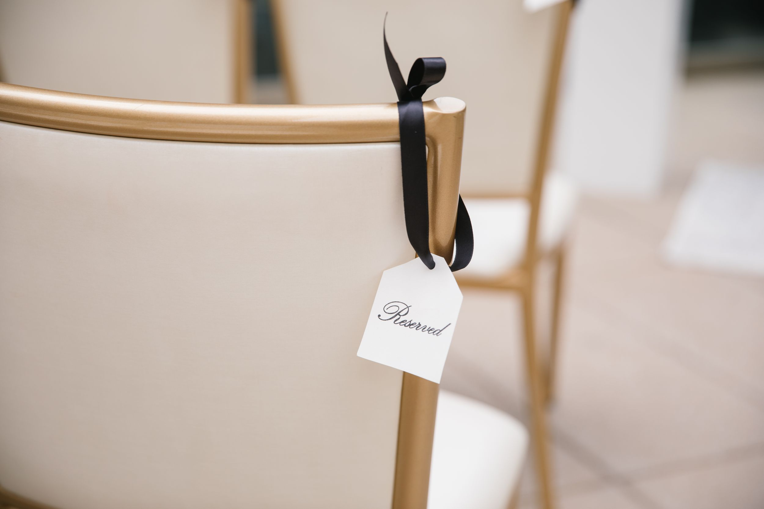 close up of reserved sign hung on chair with black ribbon