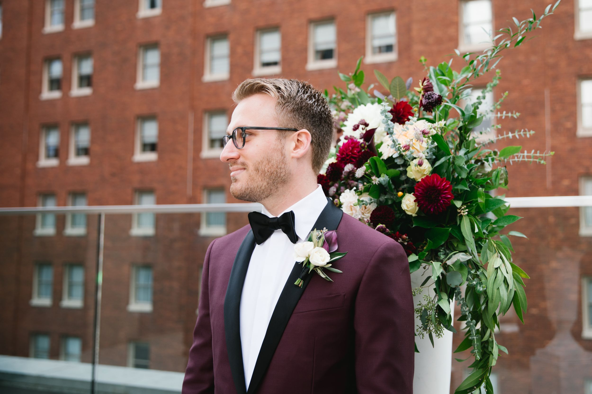 groom looking at bride walking down the aisle with building behind him