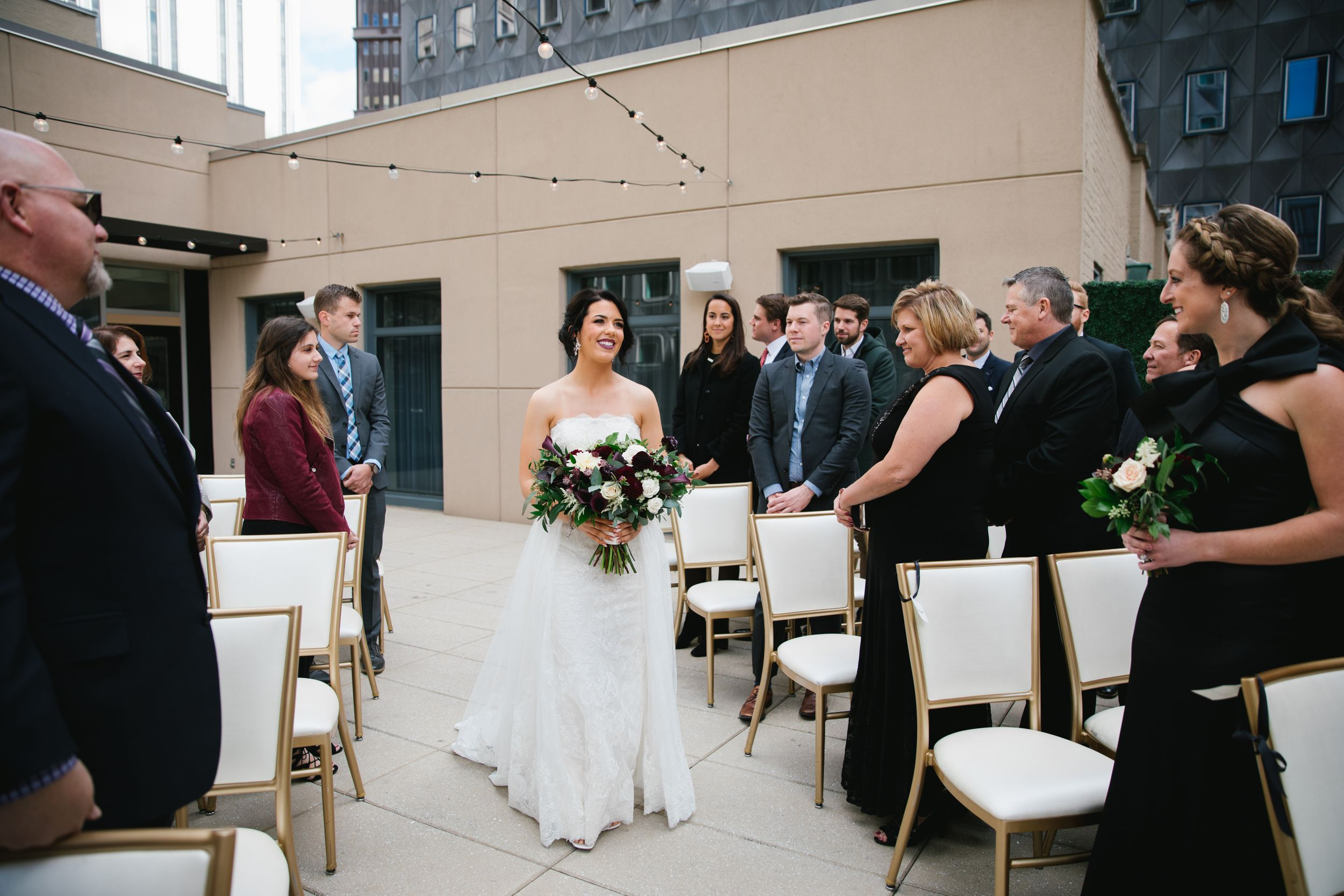 bride walking down aisle smiling with friends and family looking on