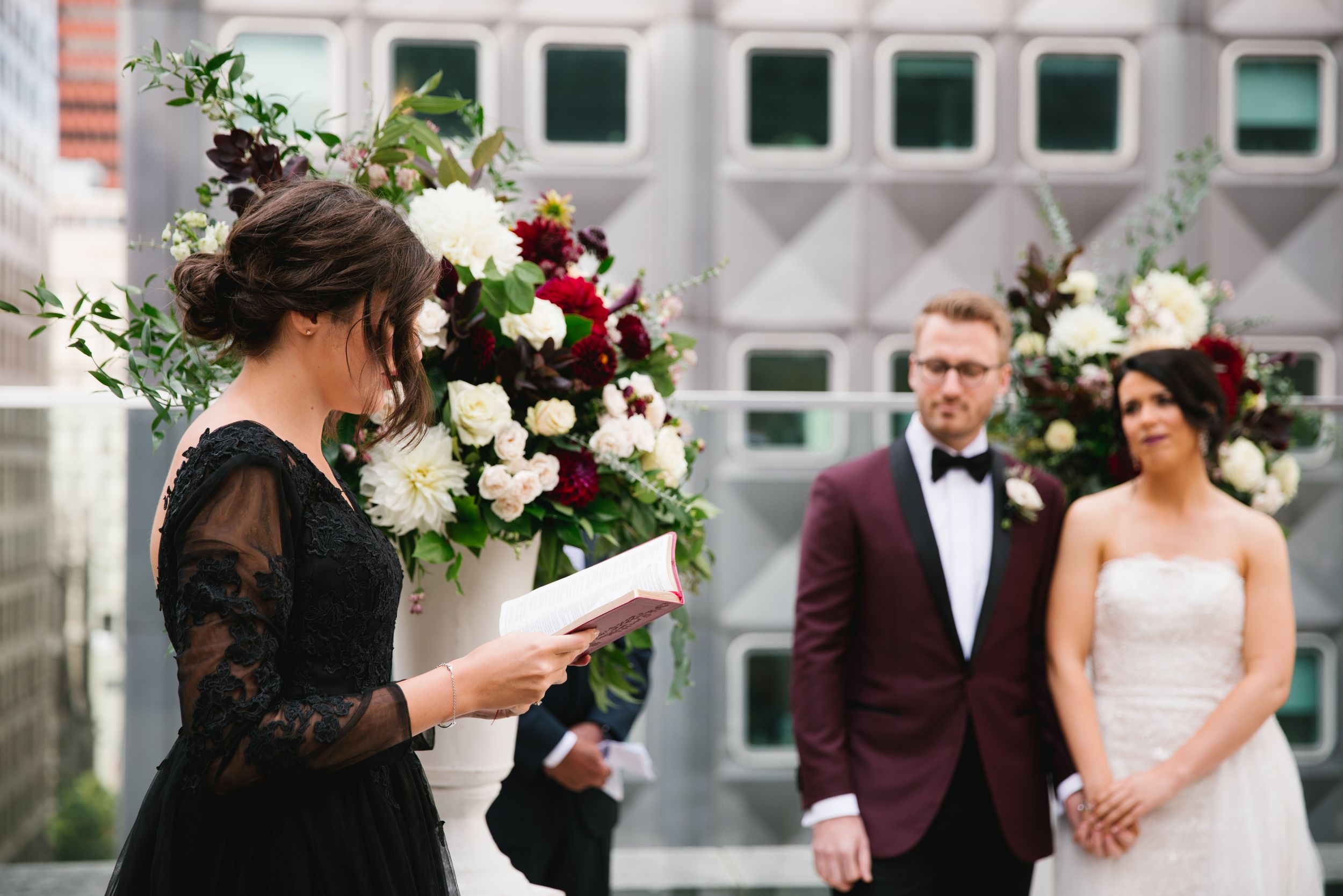 bridesmaid reads while bride and groom look on and hold hands during ceremony