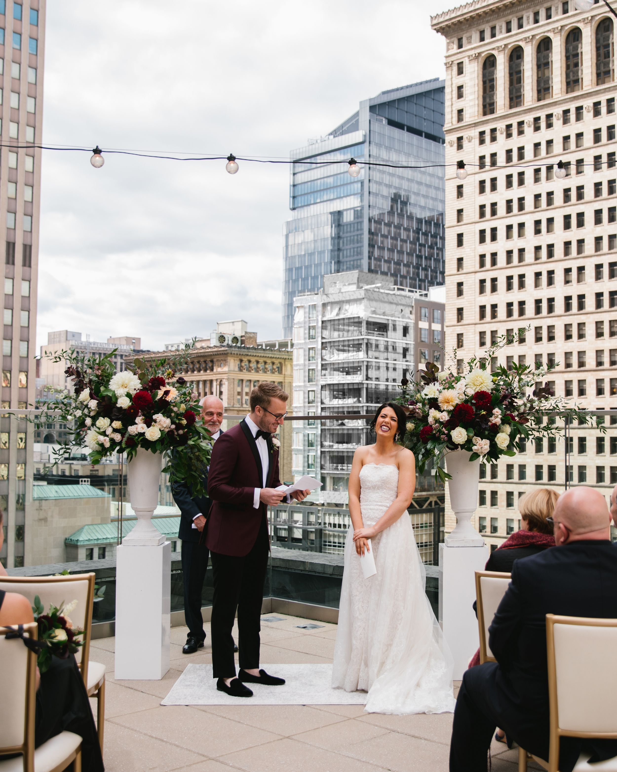 bride laughing while groom reads his vows at rooftop ceremony overlooking the city skyline toronto