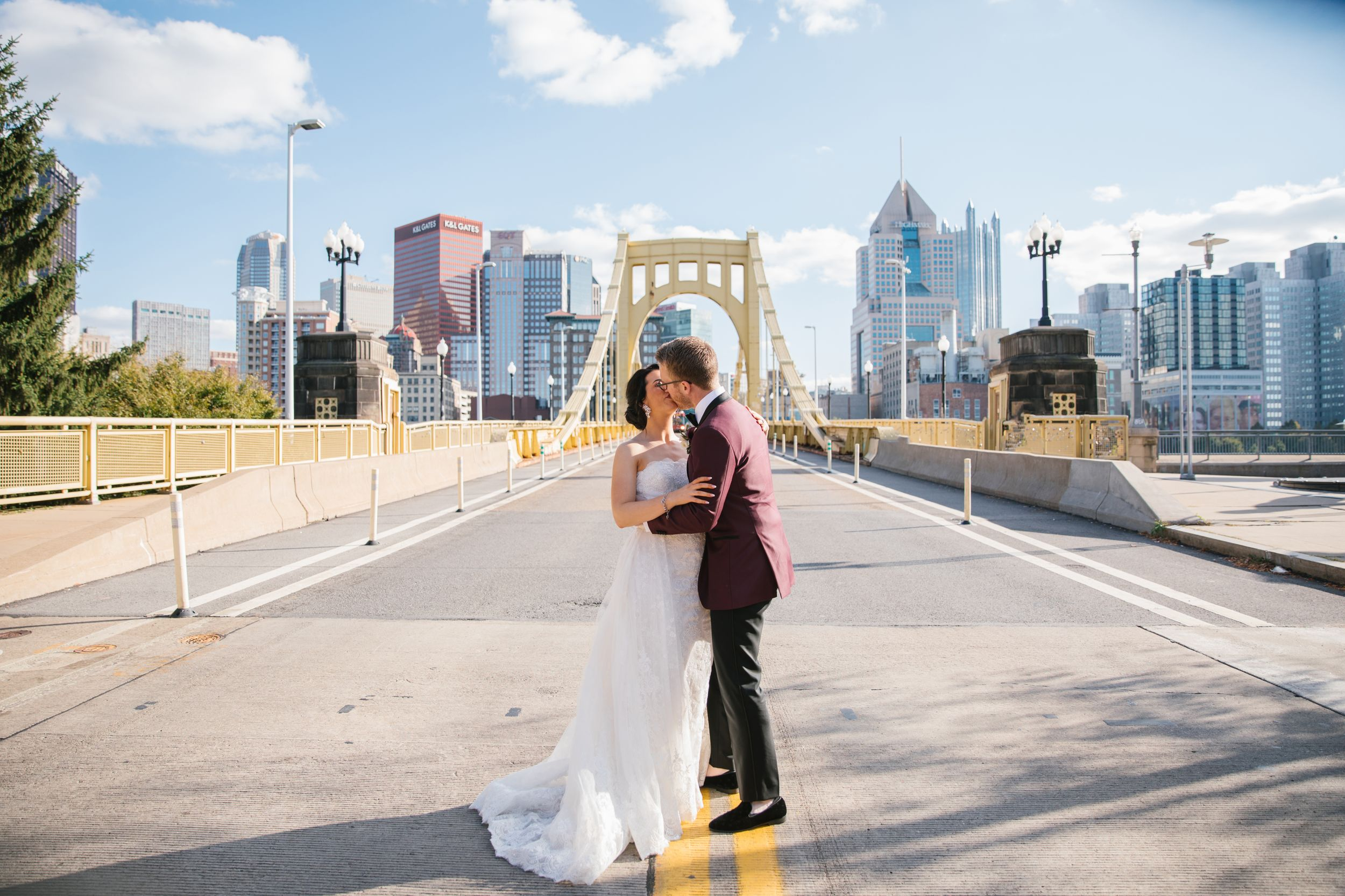 bride and groom kiss on yellow bridge in pittsburgh