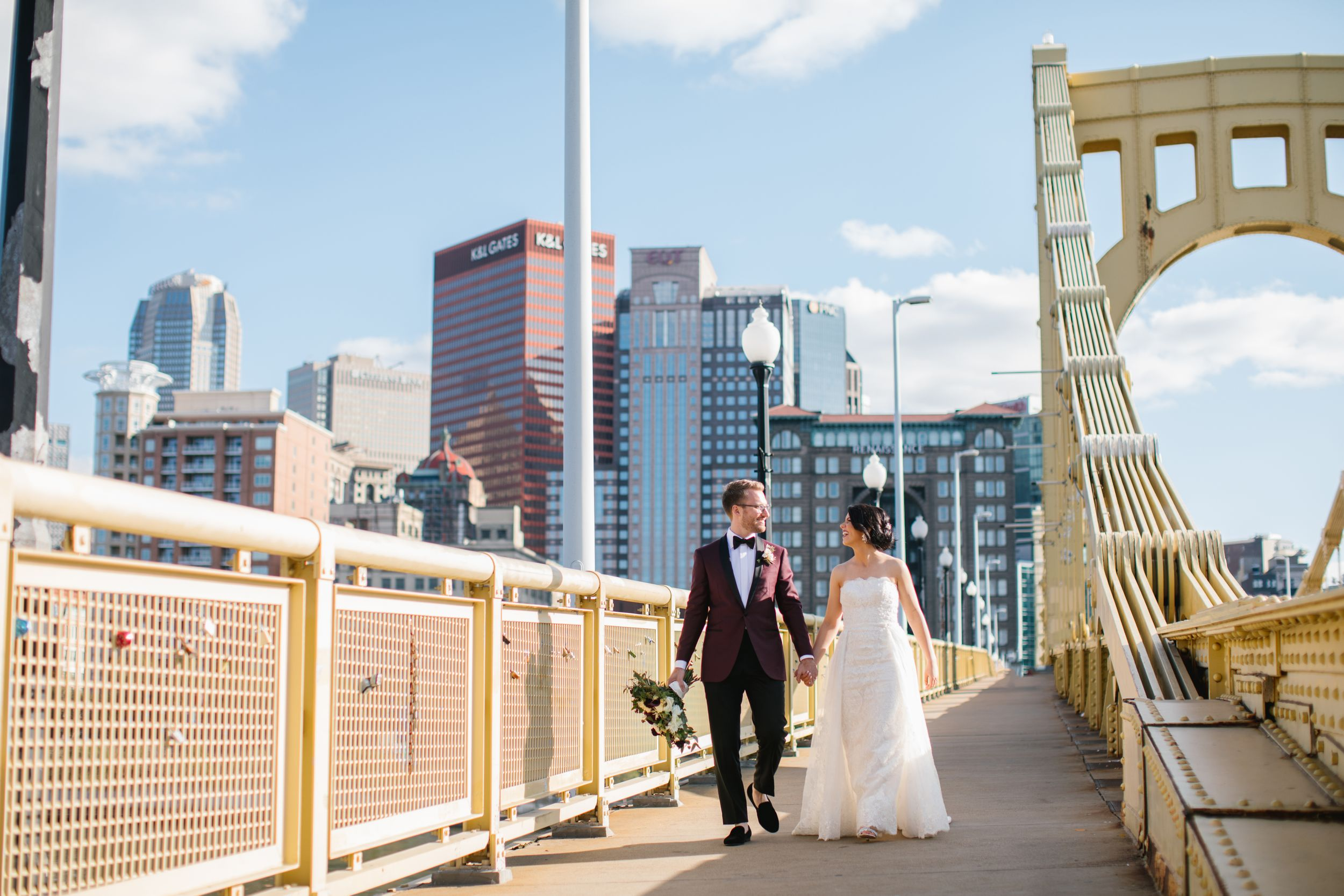 bride and groom walk on yellow bridge in pittsburgh city pennsylvania wedding