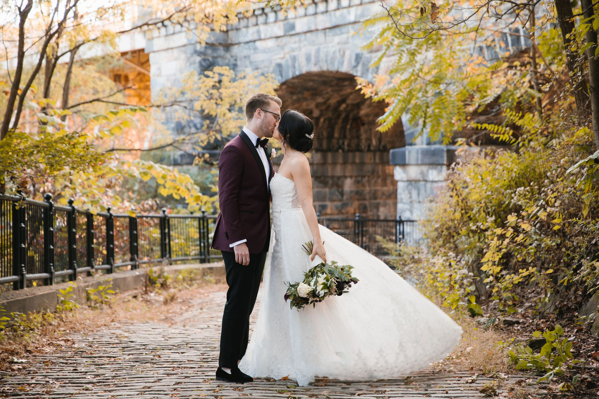 bride and groom kiss schenley park pittsburgh with bridge behind them and her dress is flying
