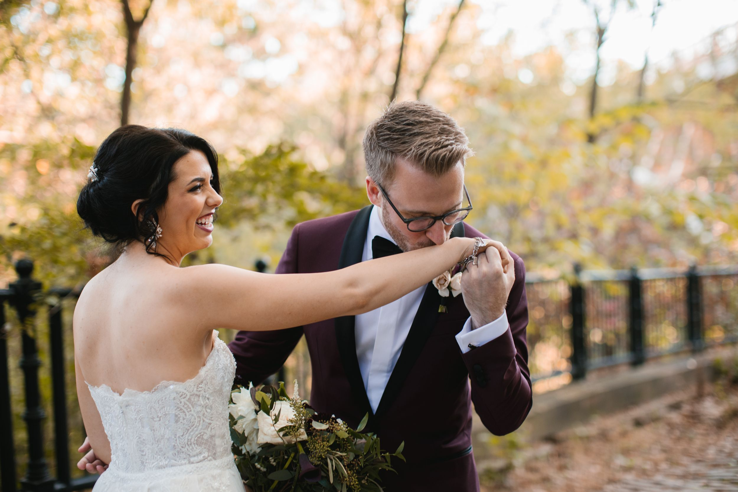 groom kissing brides hand while she laughs in park during fall