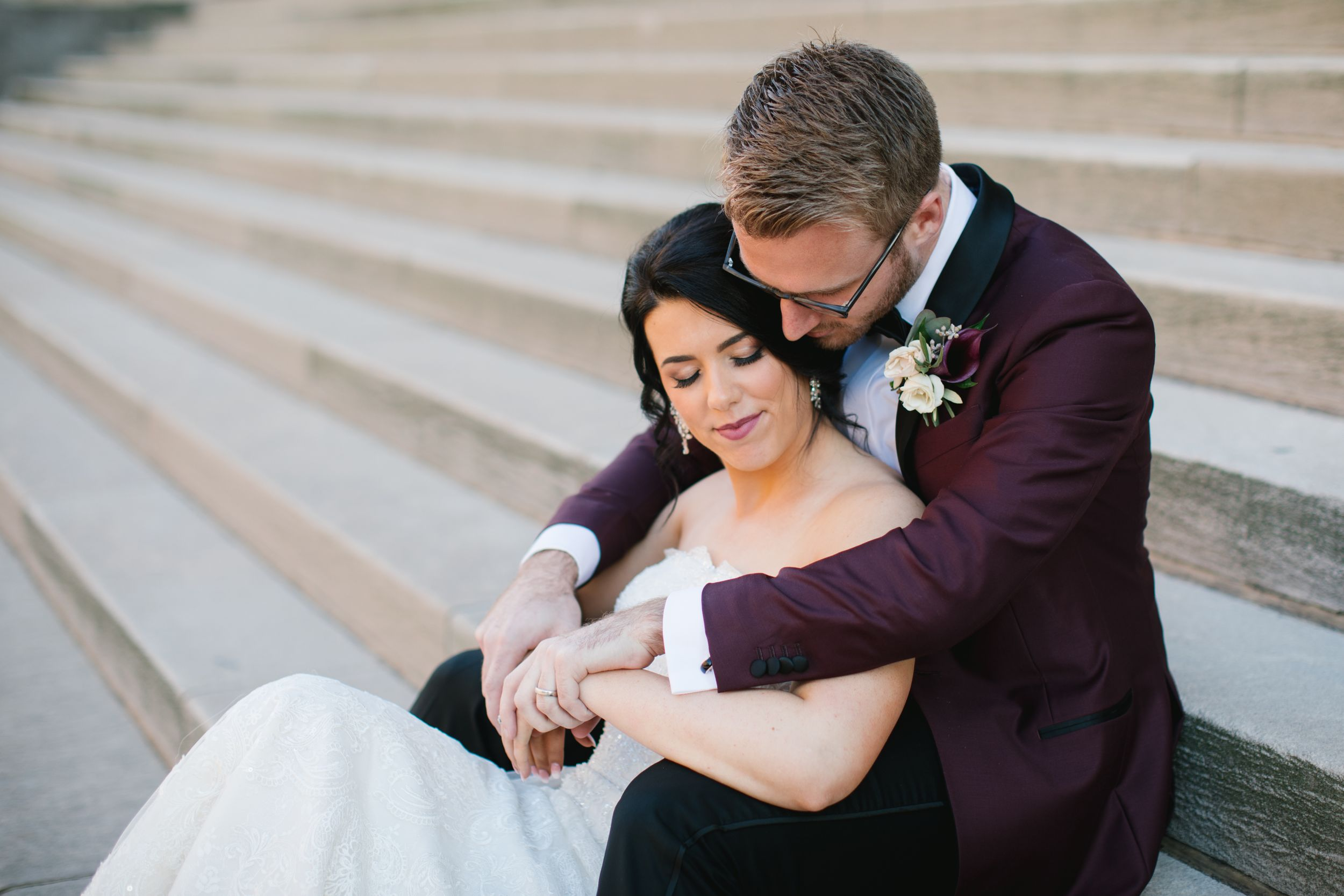 bride and groom hugging and sitting on concrete steps