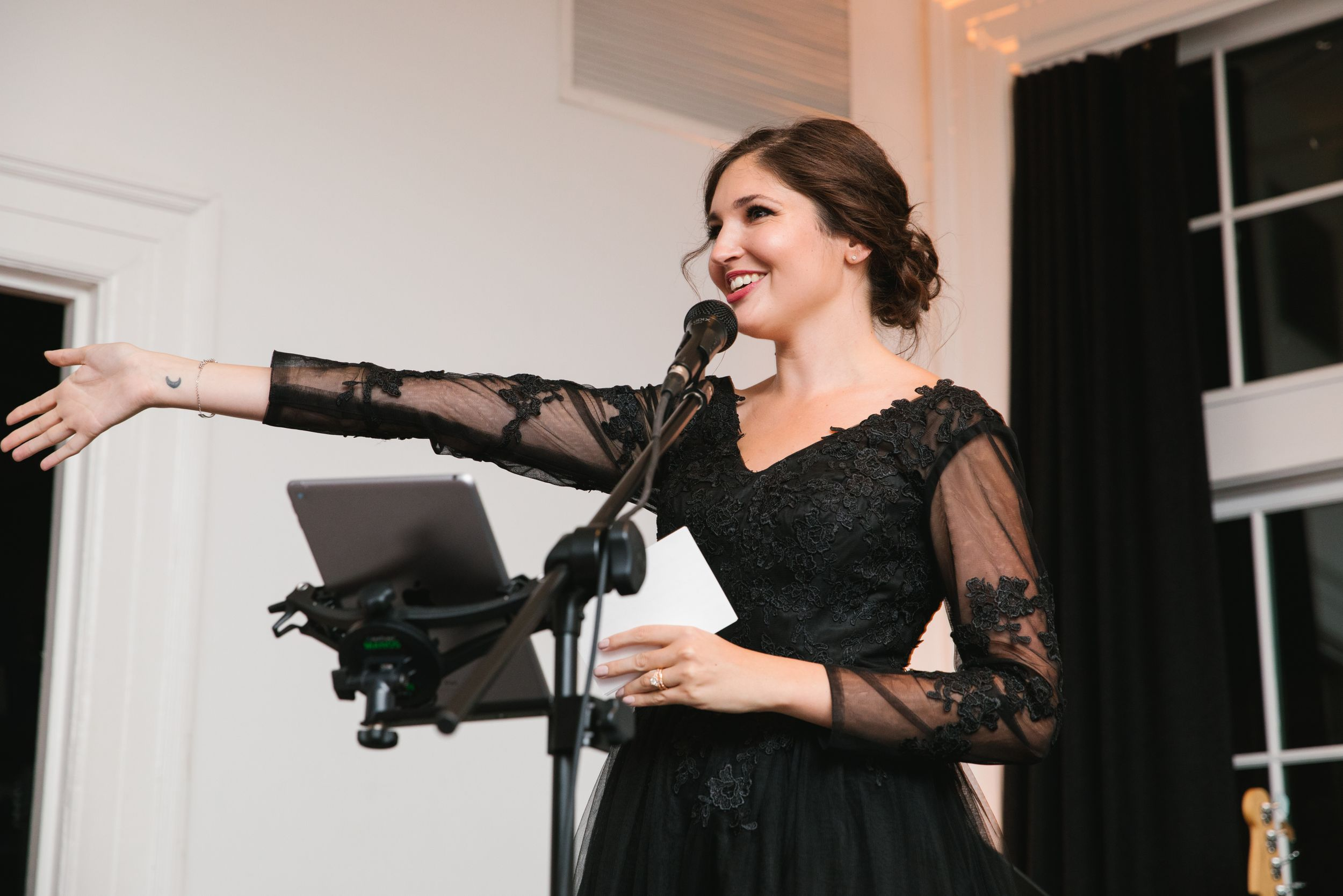maid of honour in black dress making speech and pointing at bride and groom