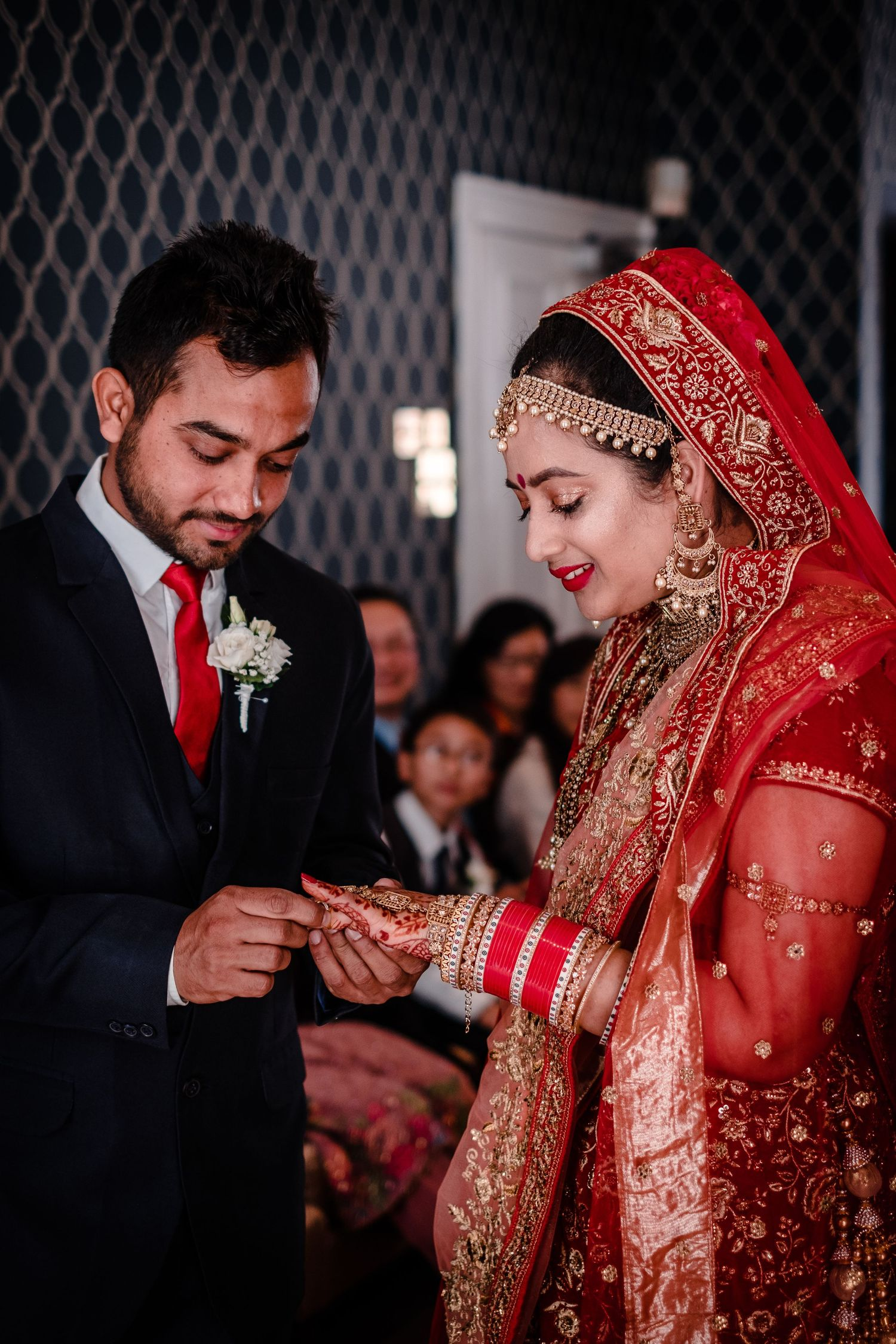 groom puts bride ring on her finger