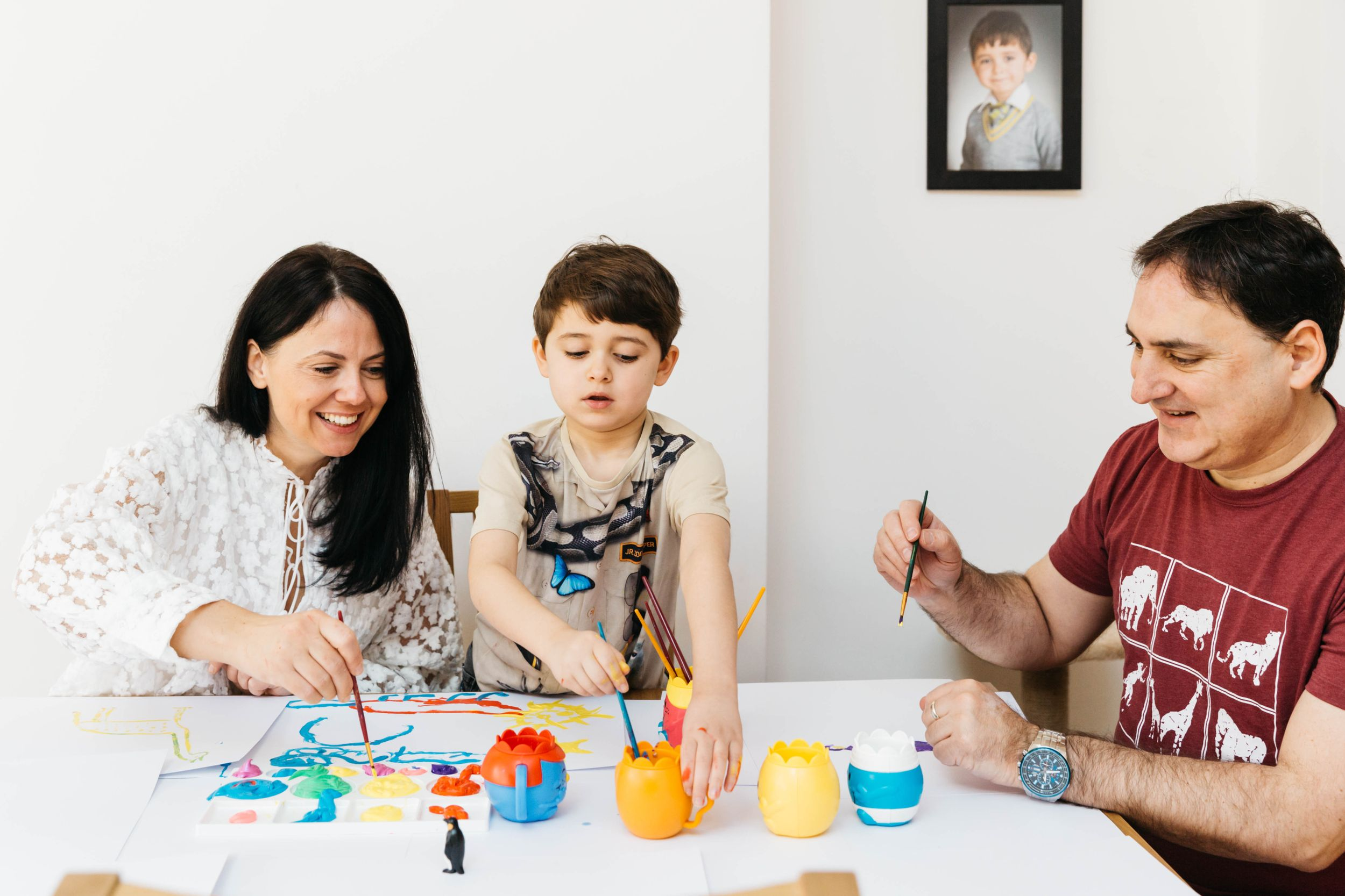 family of three at home with dog painting