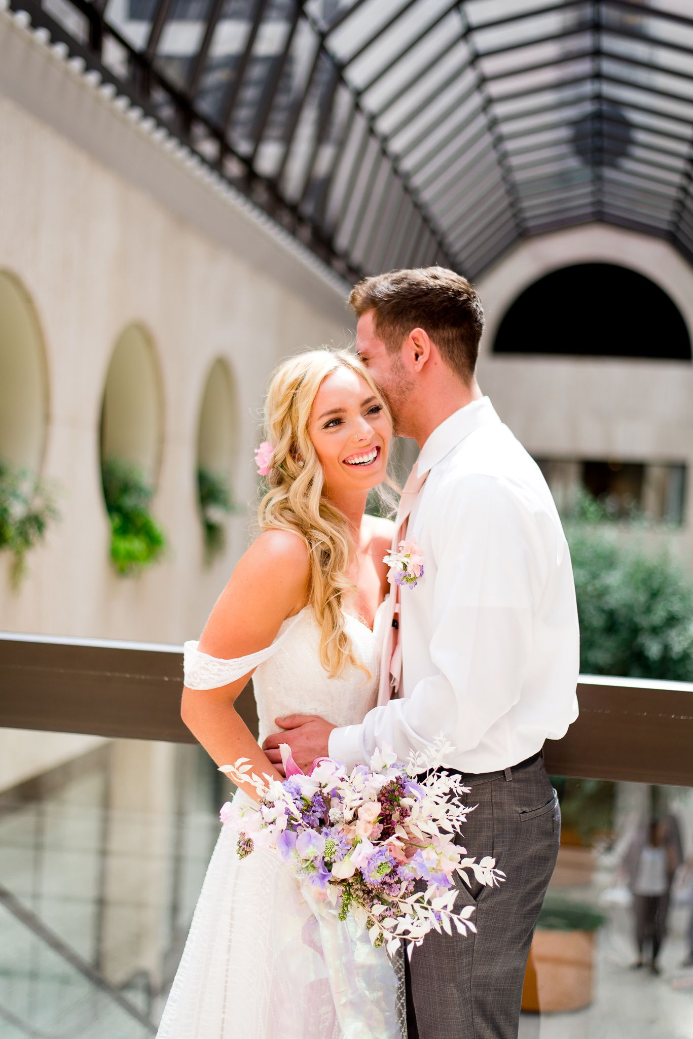bride and groom laughing in atrium of The Center Cincinnati for spring wedding