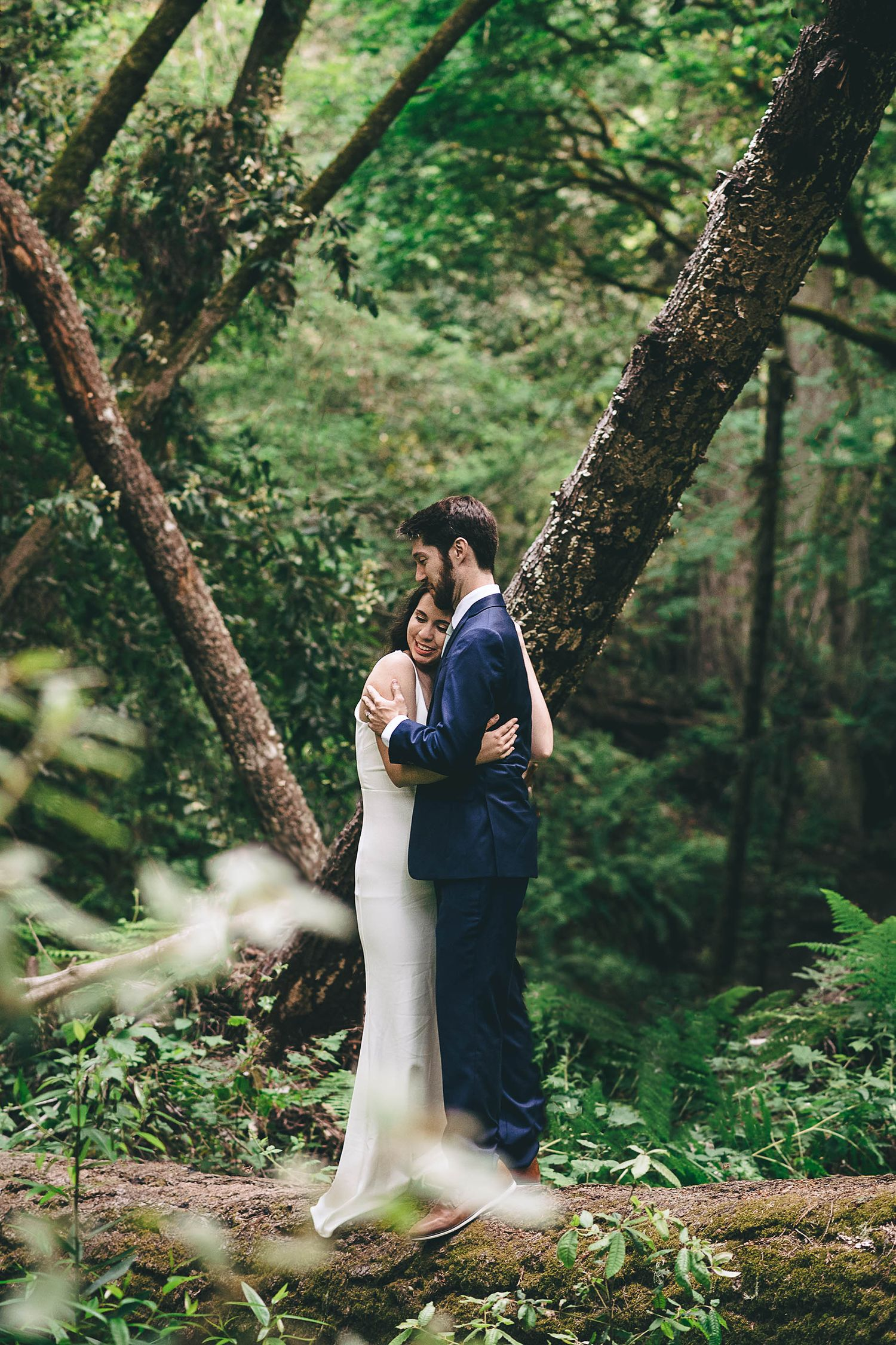 Bride and groom standing on a long in the redwood forest at their Big Sur wedding