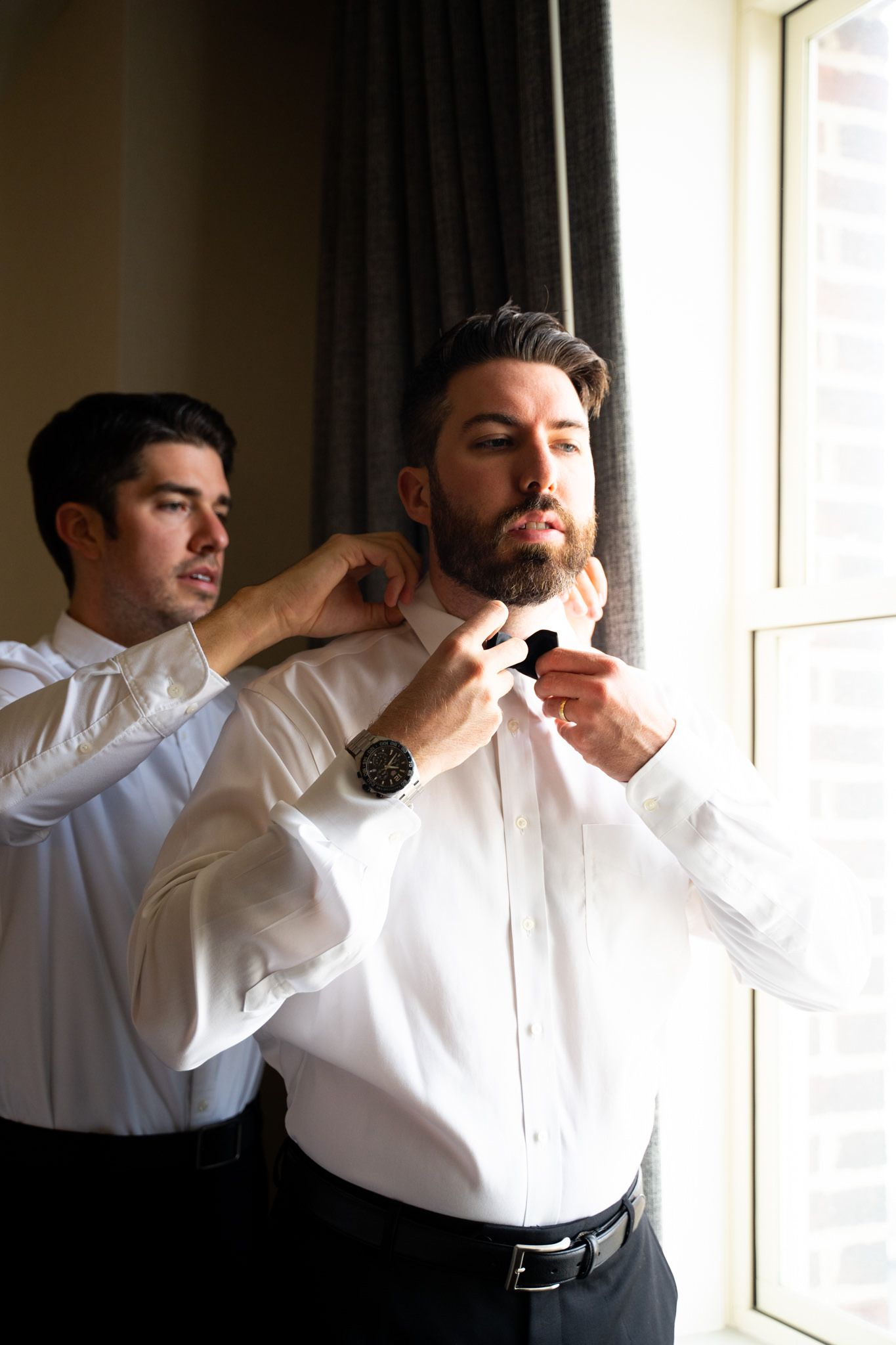 brunette groom fixing bowtie near a window for Chicago wedding