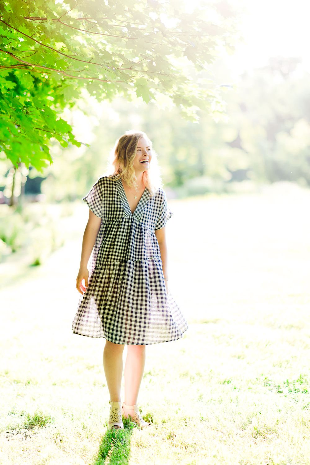 young woman in blue and white checkered dress laughing at sunset for senior pictures