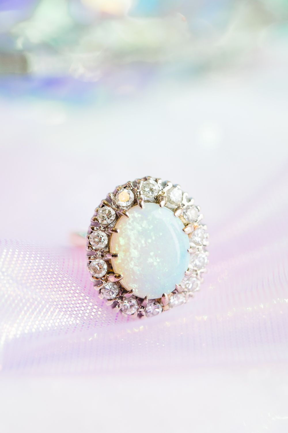 opal engagement ring on top of iridescent ribbon