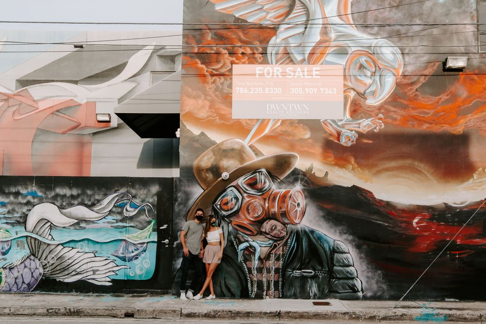 couple posing in front of a masked mural in downtown Miami