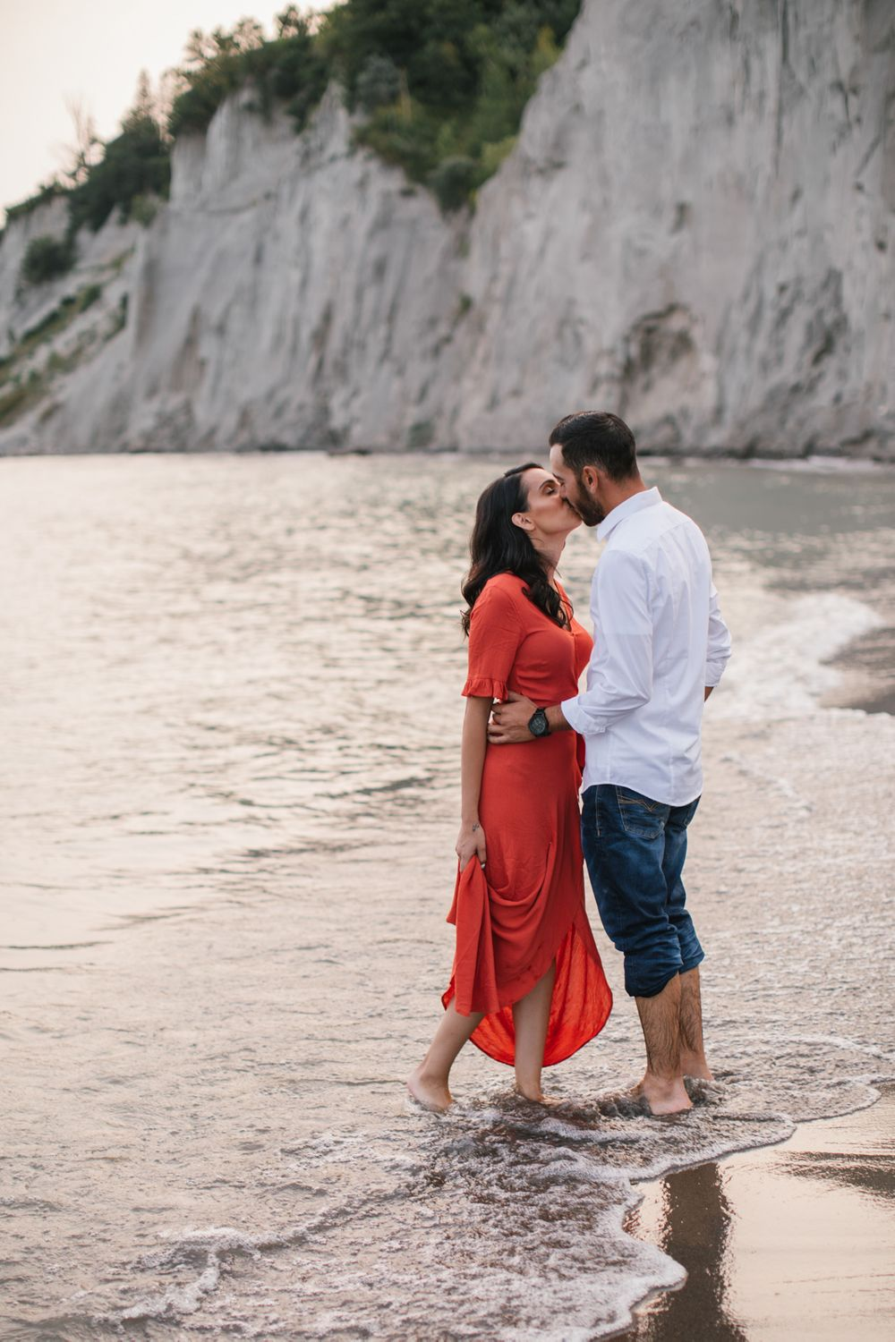 Scarborough bluffs engagement couple kissing in the water