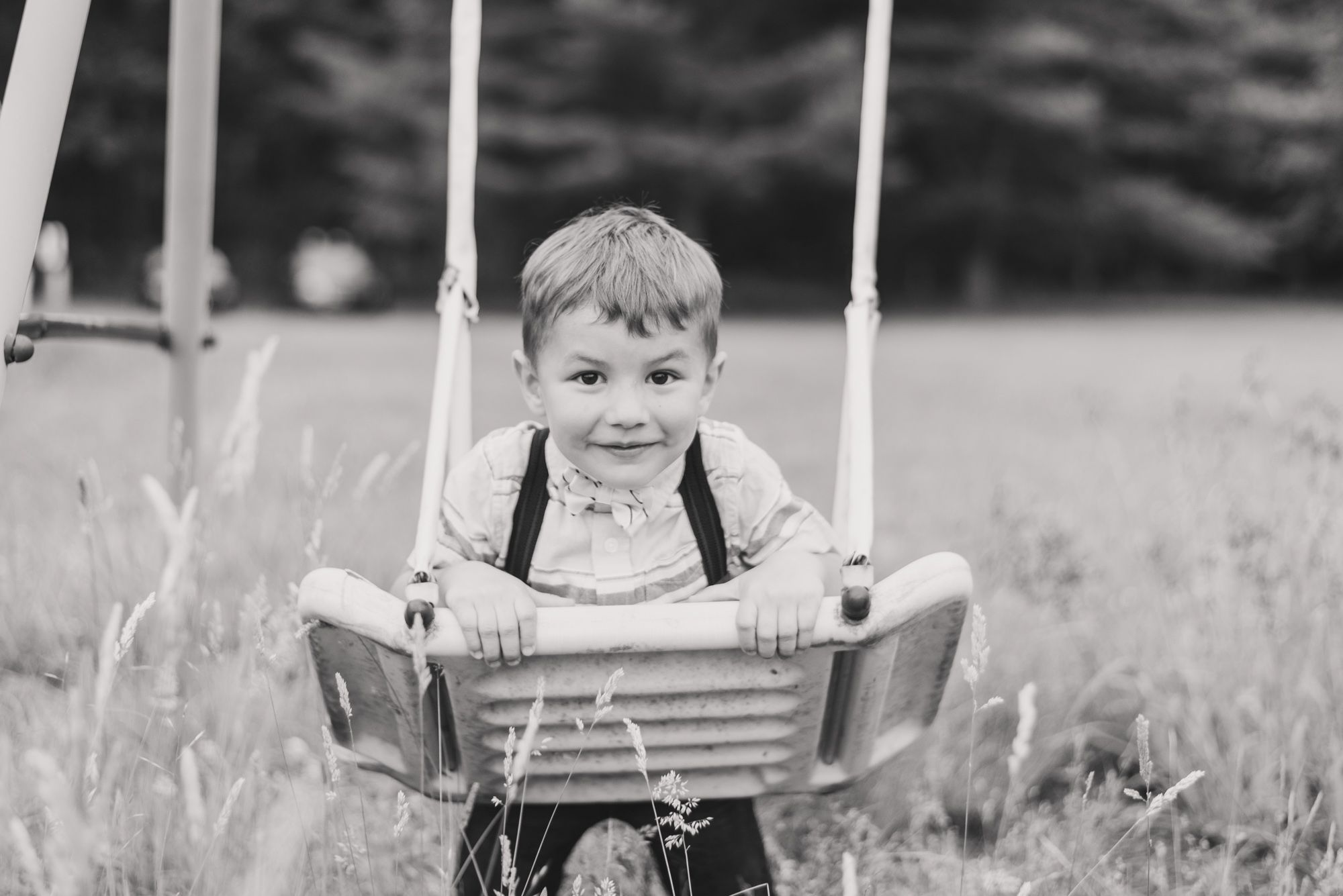 Little boy in suspenders swinging on swing set in black and white in Clarion Pennsylvania