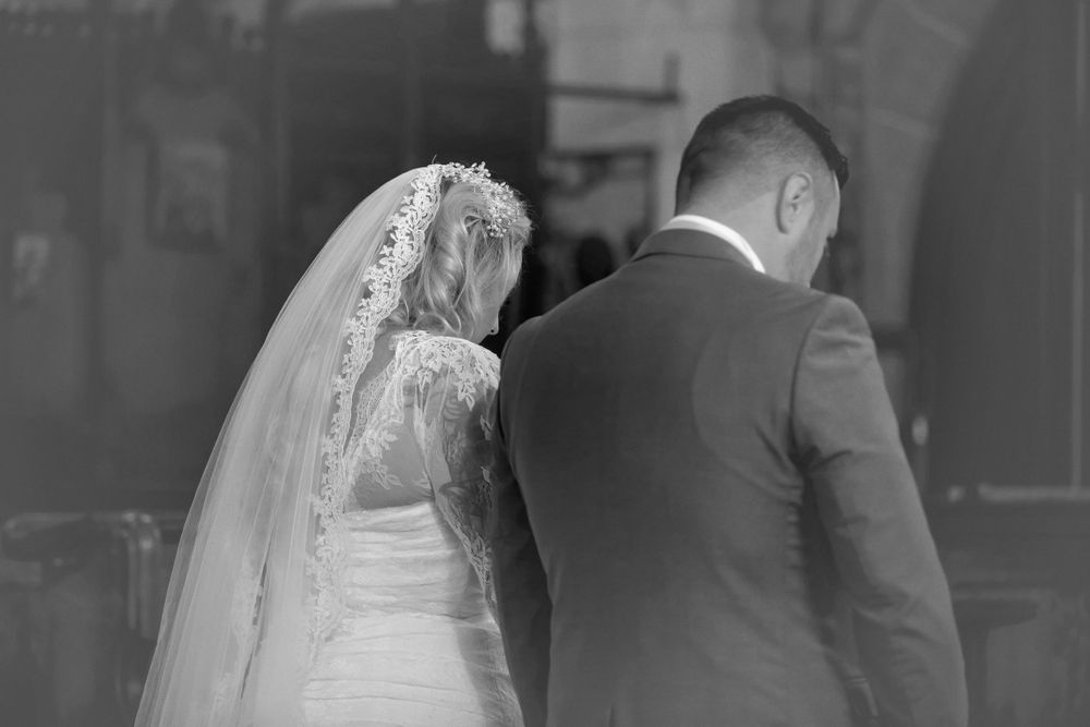 black and white image of bride and groom at alter in church with heads bowed.