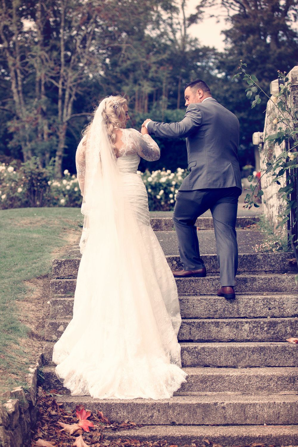 Groom assisting his bride up some steps at Clowance Estate.