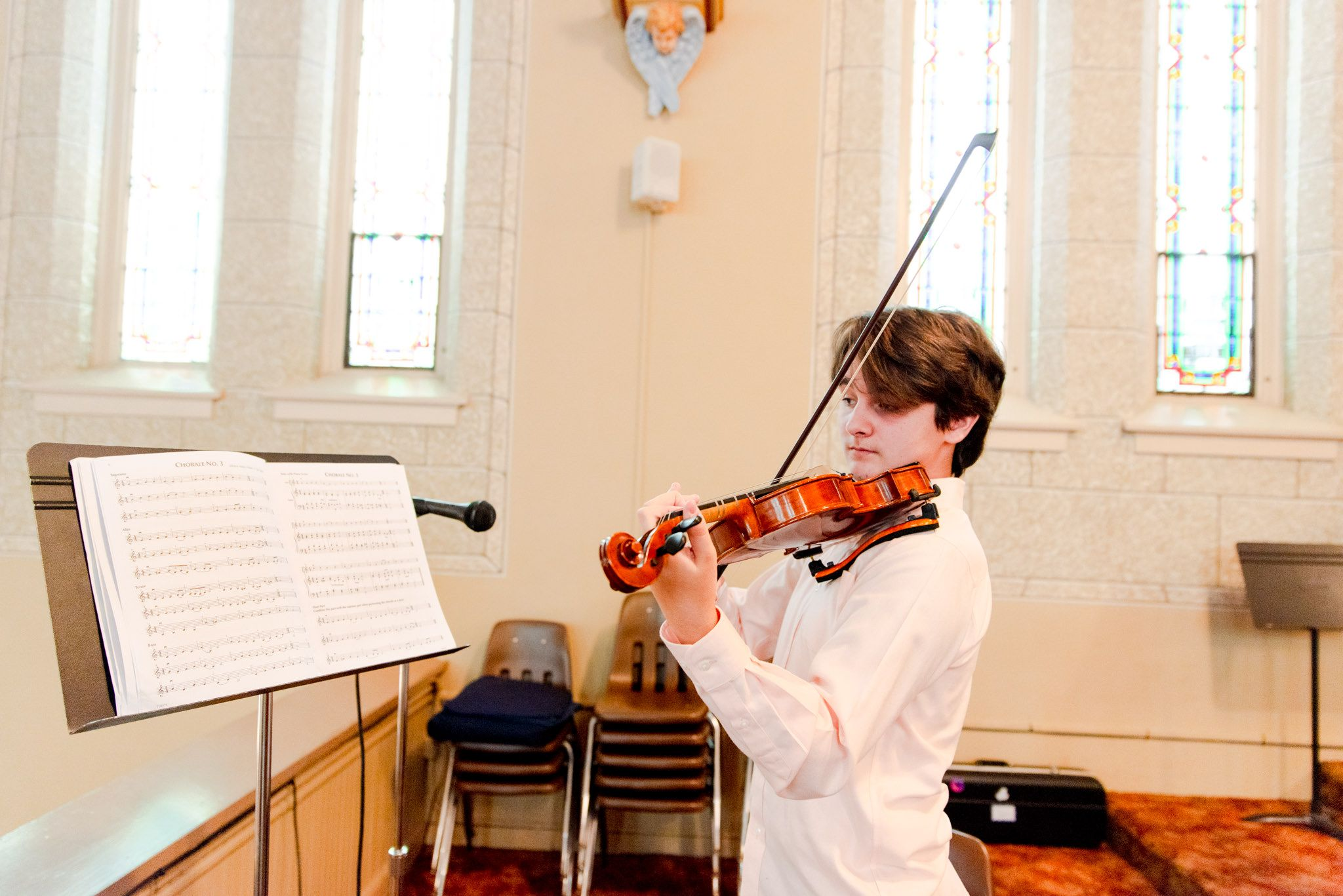 young man playing violin inside church for downtown STL wedding