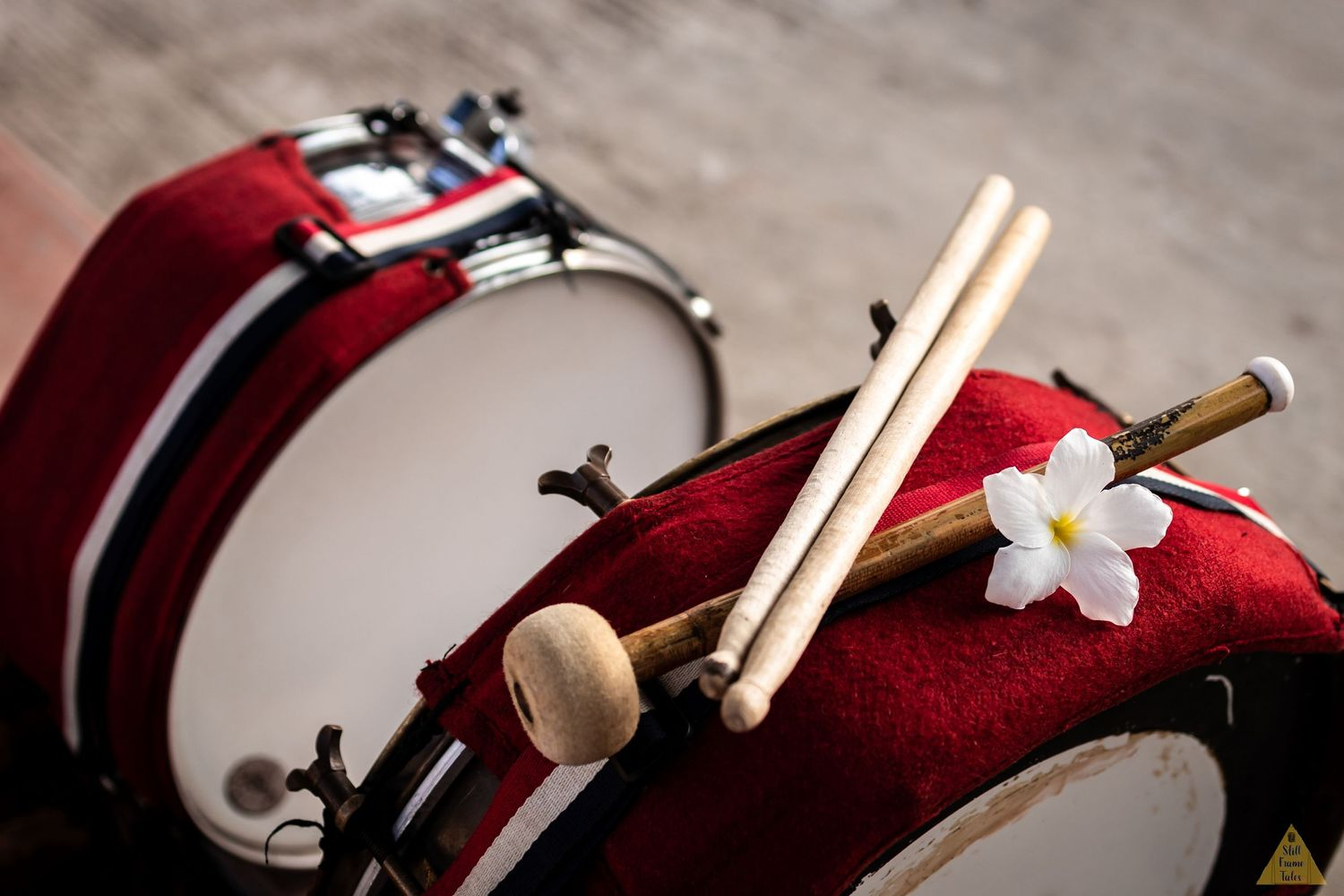 Drum stick on drums with white flower at a destination wedding