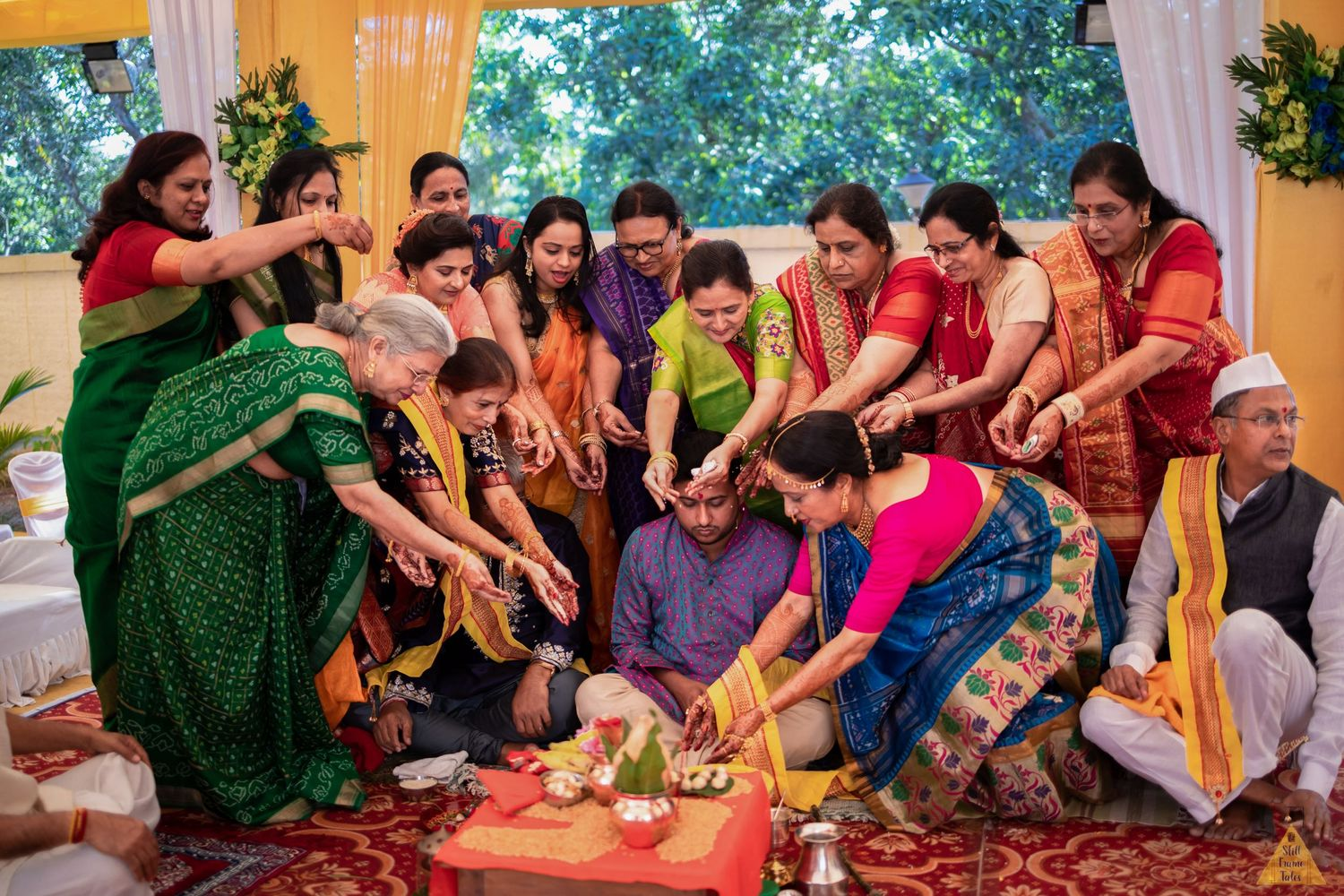Close relatives of groom performing a wedding ritual with groom