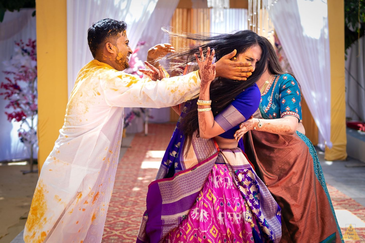 Groom grabbing cousin to put some haldi on her face during destination haldi ceremony