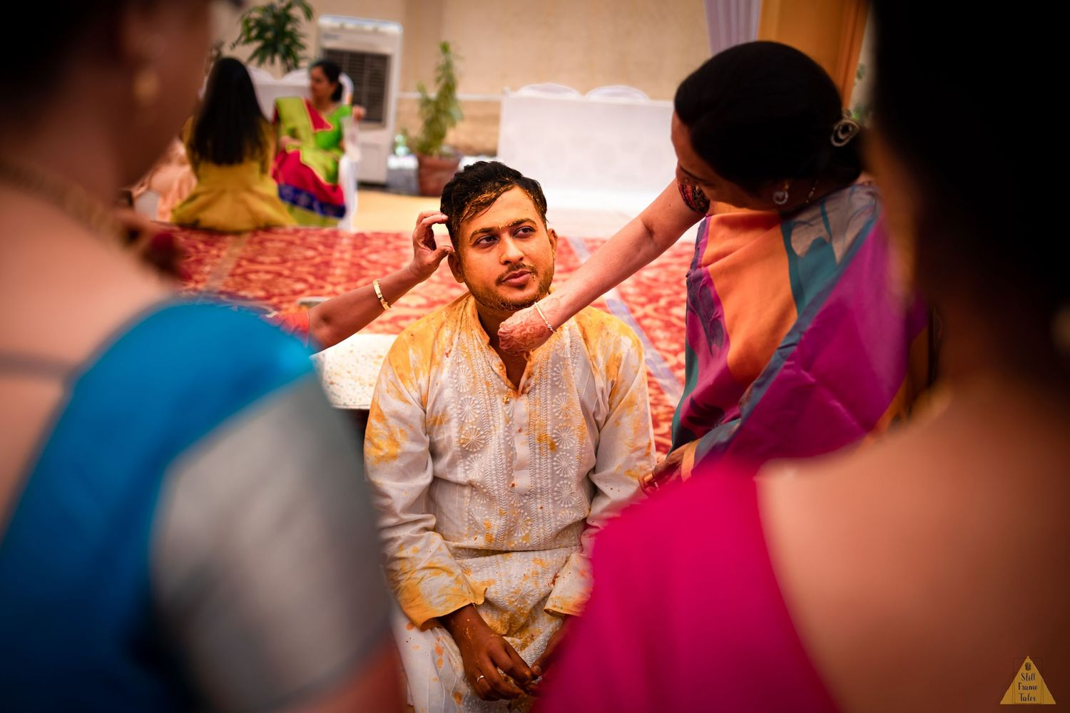 Relatives cleaning haldi from groom's face at a destination wedding ceremony