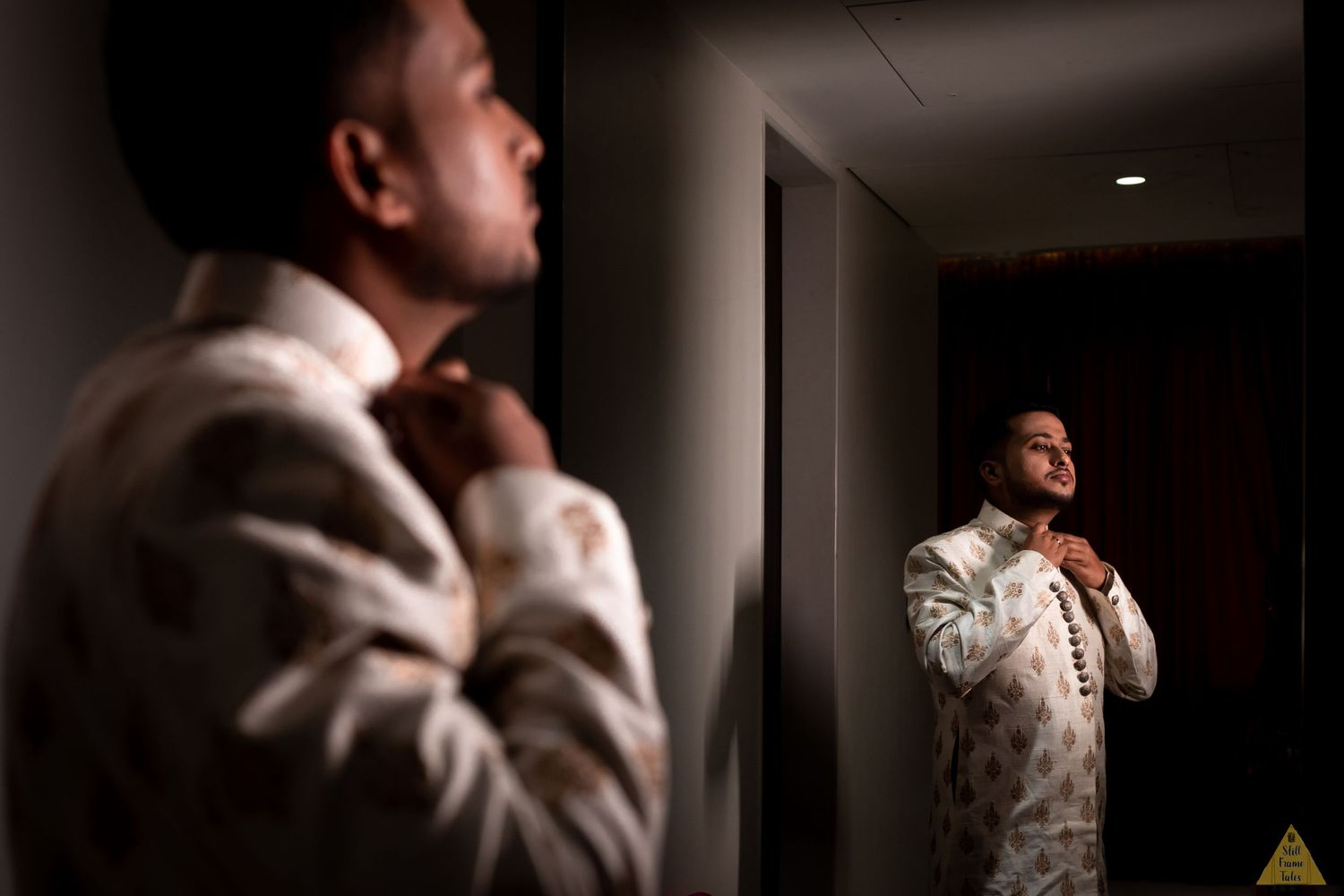 Groom adjusting his wedding dress with reflection in the mirror at a destination wedding