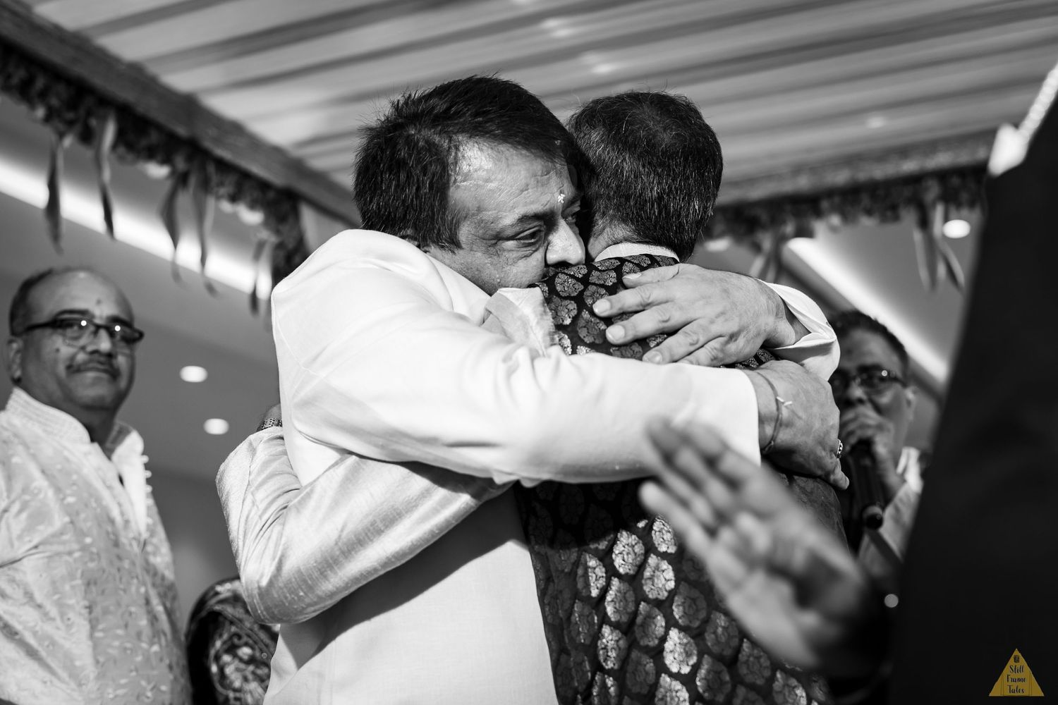 Couple fathers hugging each other at a destination wedding day ritual