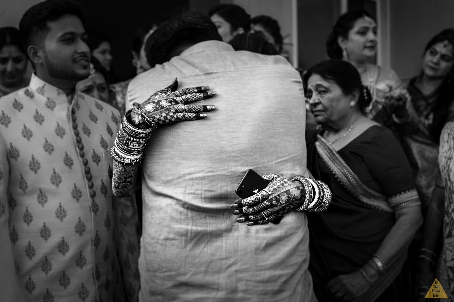 Bride tightly hugging her father while bidding goodbye in a black & white picture