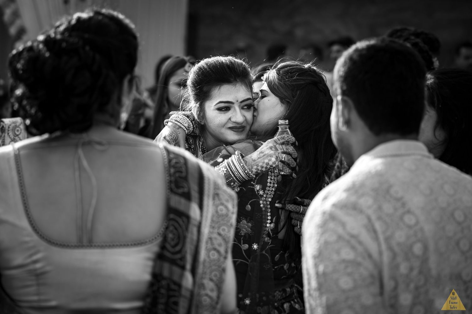 Bride's friend kissing on her cheeks at emotional viddai ceremony