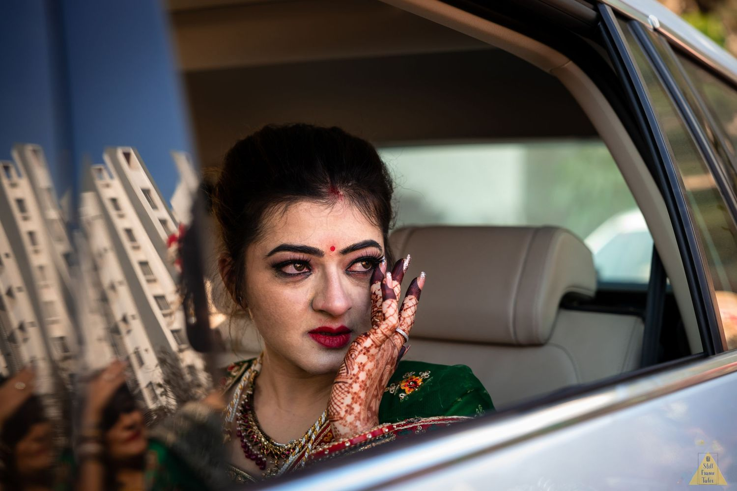 Bride wiping her tears while sitting in a car window at a destination wedding emotional viddai