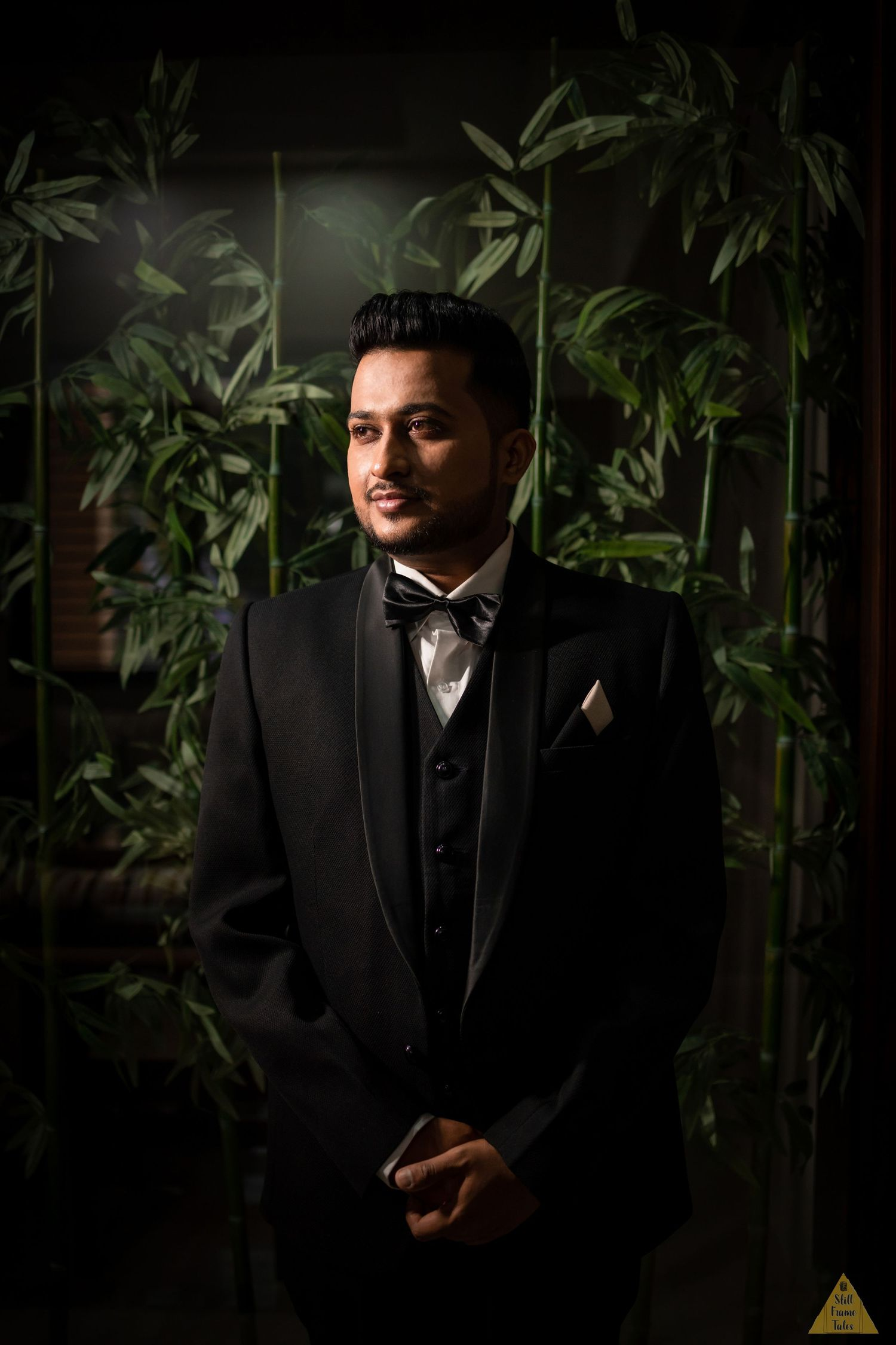 Groom posing for a solo portrait with green tree background