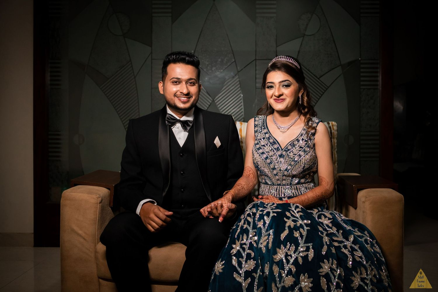 Couple sitting on a couch and posing for a couple shoot at their destination reception