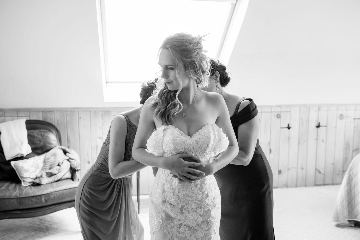 mom and sister helping bride with dress