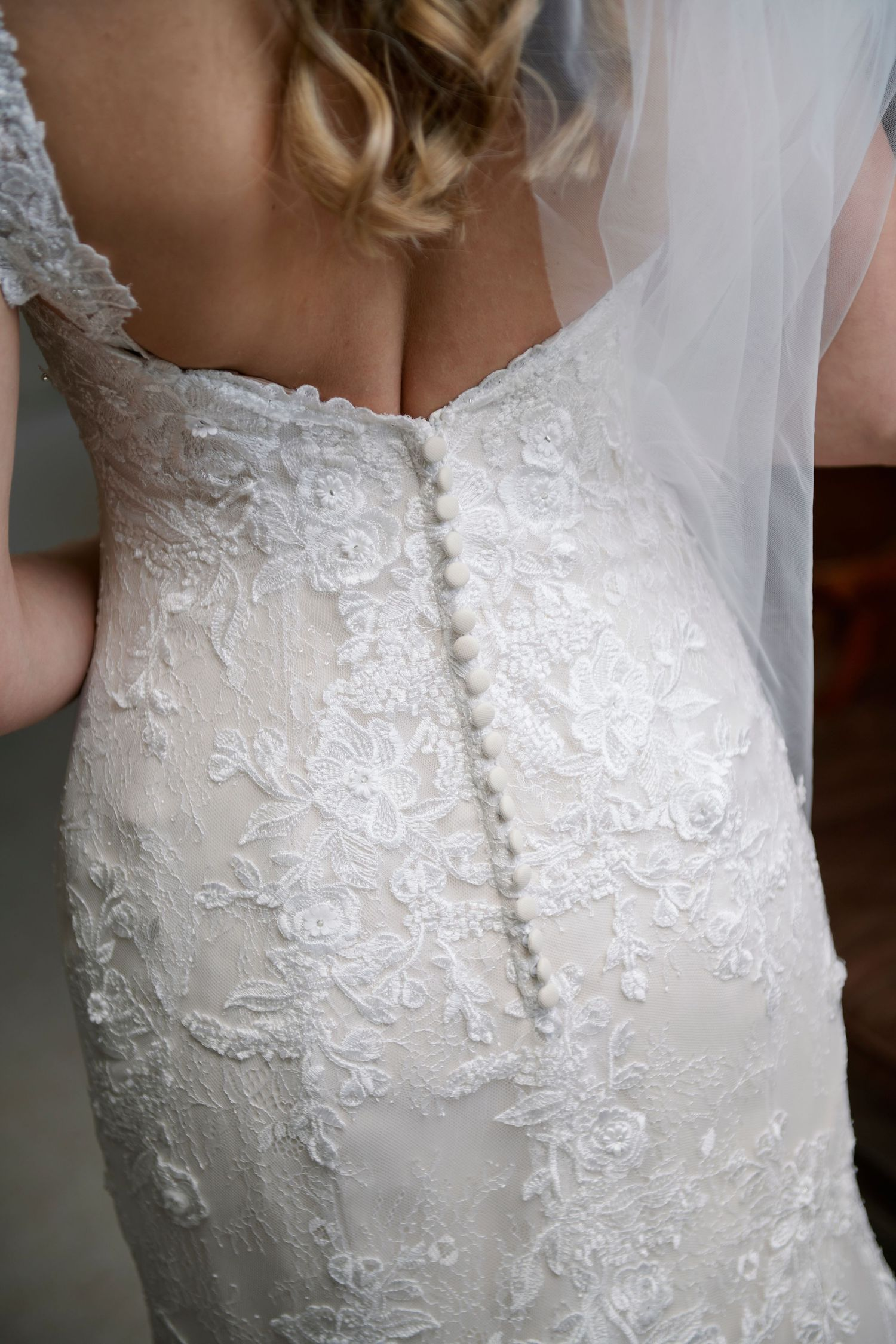 bride's dress back detail before backyard farm wedding