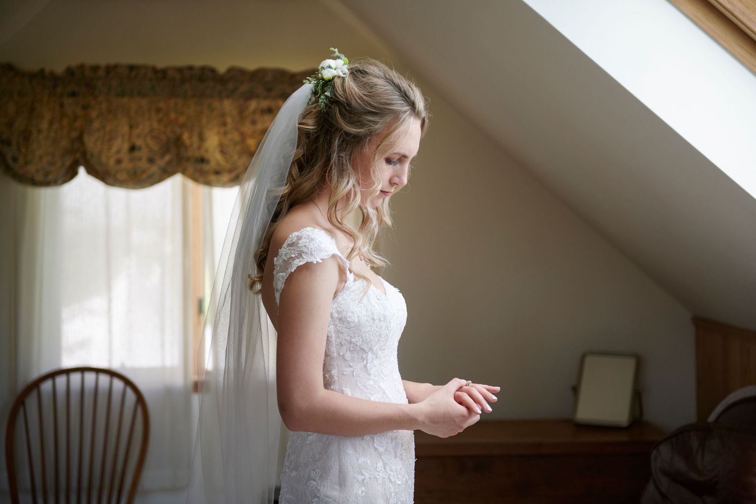 bridal portrait with bride looking at ring before backyard farm wedding