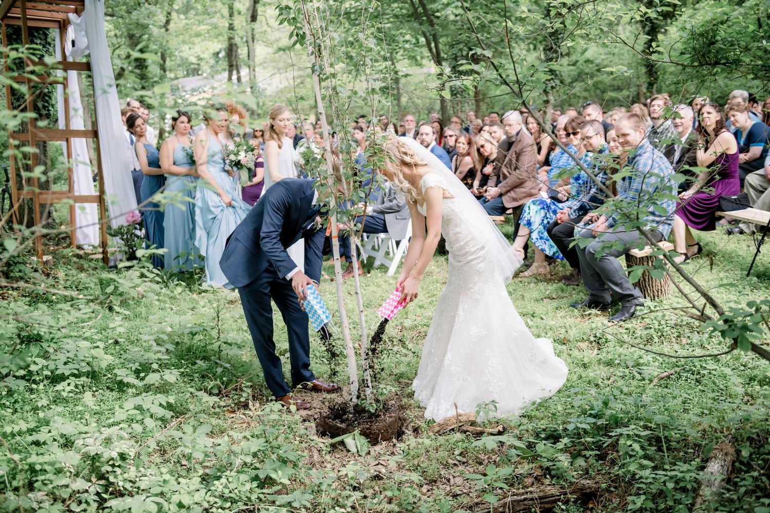 bride and groom planting a tree during their backyard farm wedding in woods