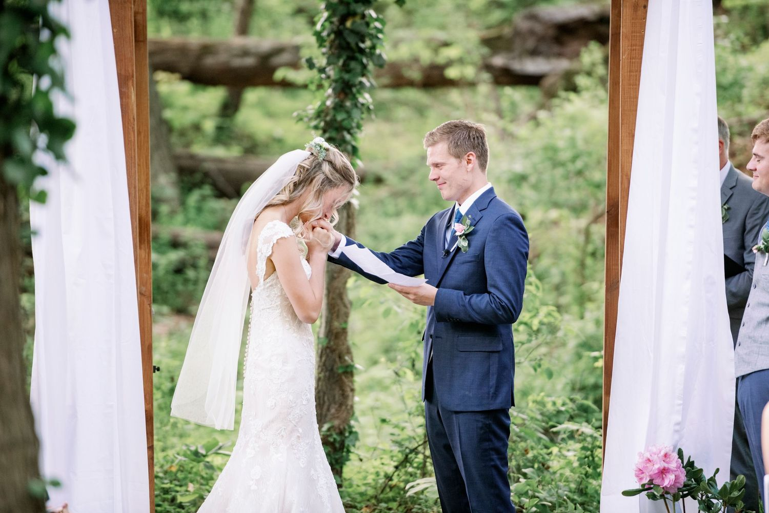 bride kisses groom's hands while he says his vows at their backyard farm wedding in woods