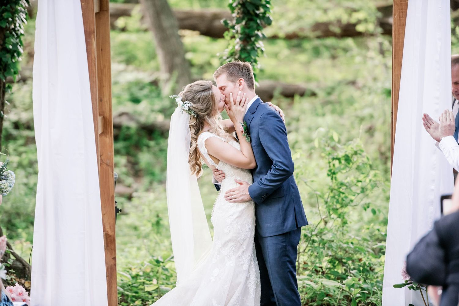 bride and groom's first kiss during a backyard farm wedding in woods