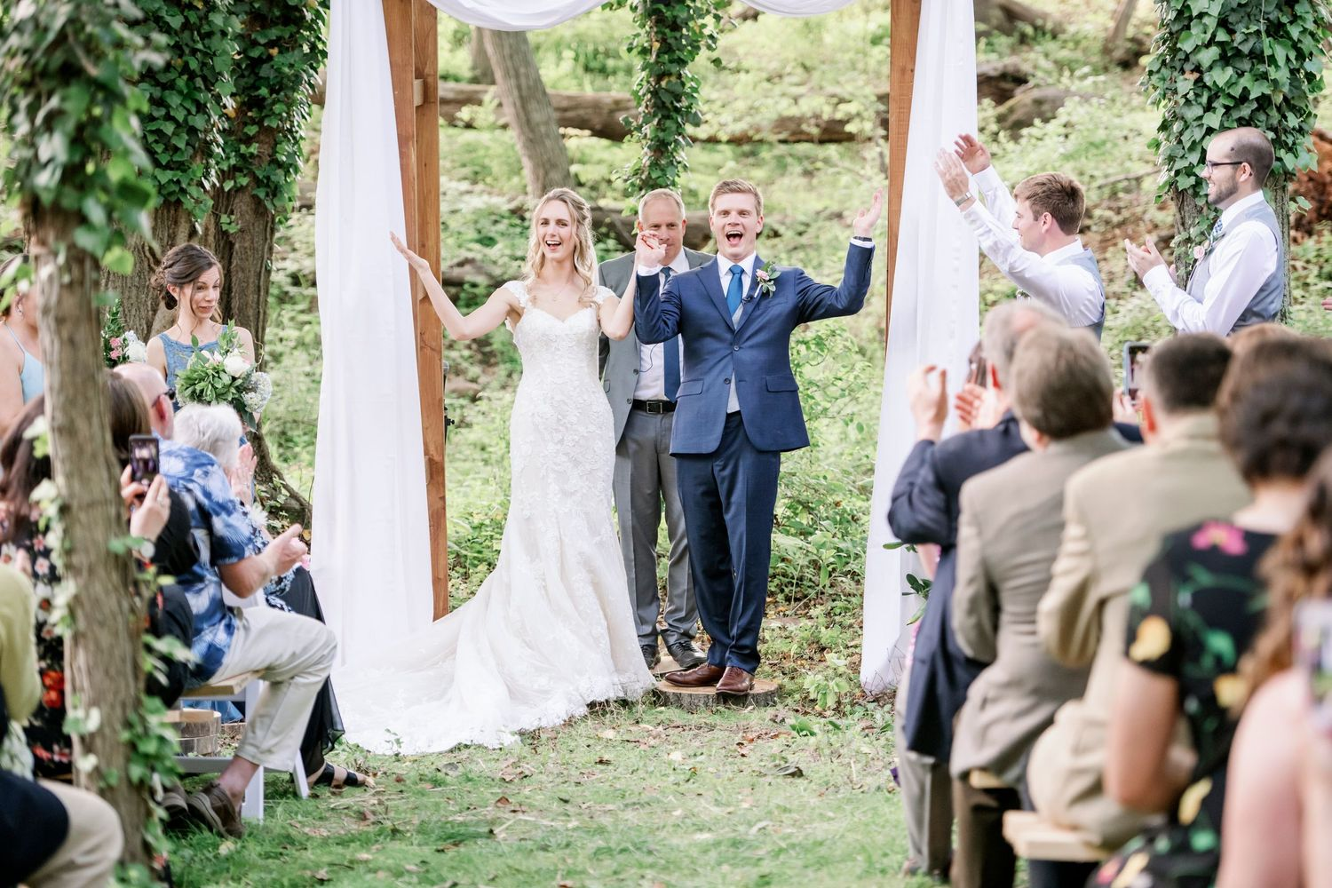 bride and groom celebrate with arms raised in their backyard farm wedding in woods