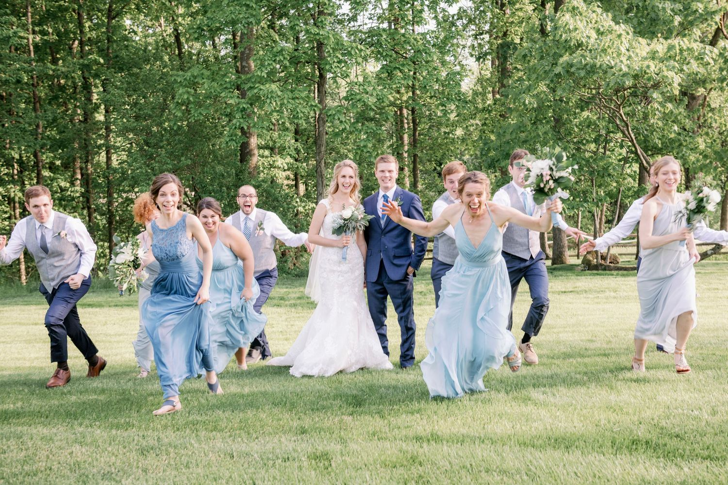 full bridal party running away during backyard farm wedding in woods