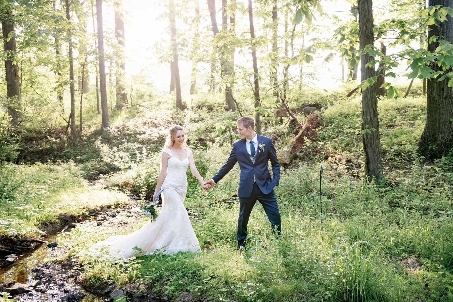 groom holding brides hand after backyard farm wedding in woods